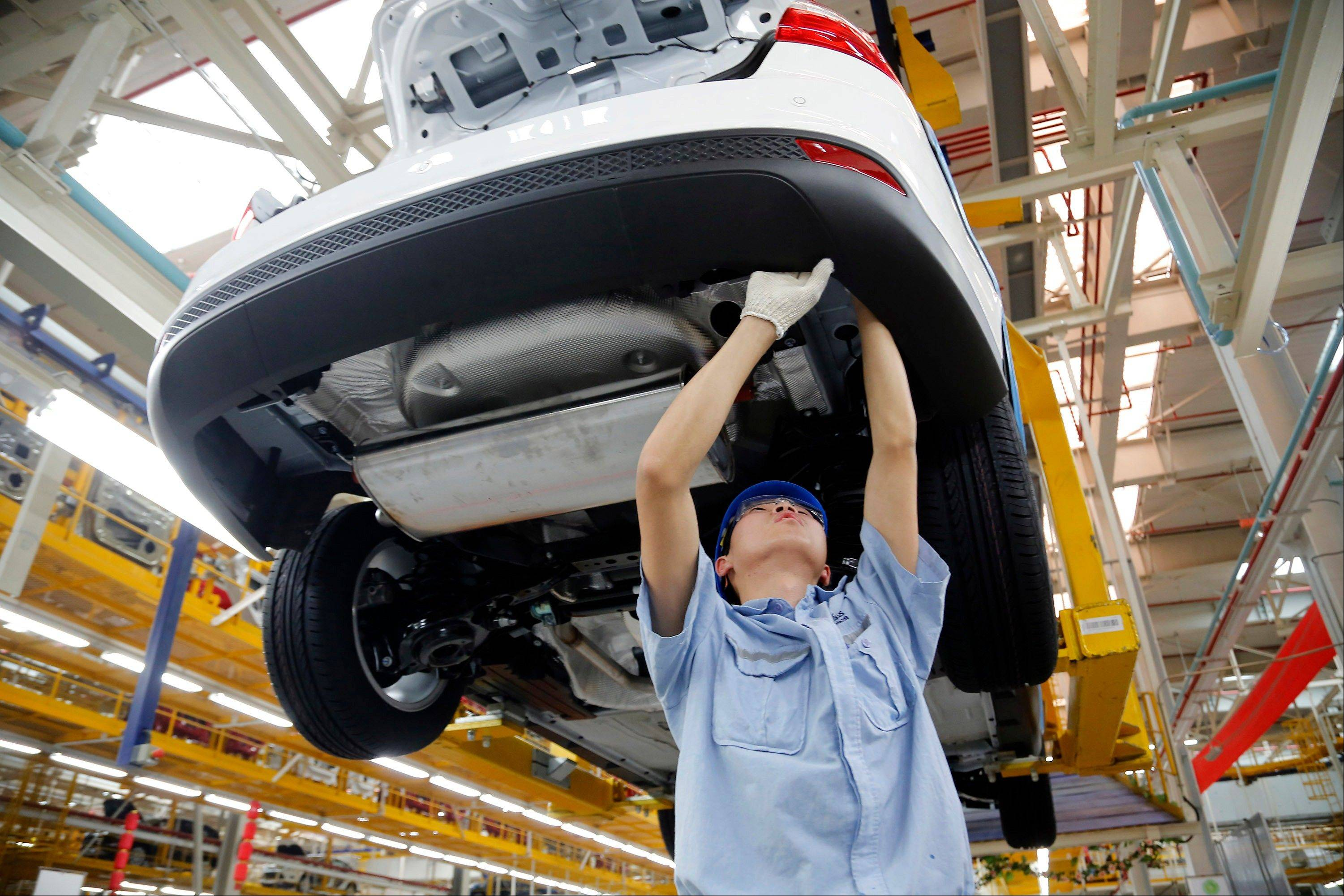 Associated Press/April 16 A worker assembles a vehicle on an assembly line at a Ford factory in Chongqing, China. China�s economy expanded 7.7 percent in the first three months of the year compared with a year earlier and that was a slowdown from its previous double-digit growth.