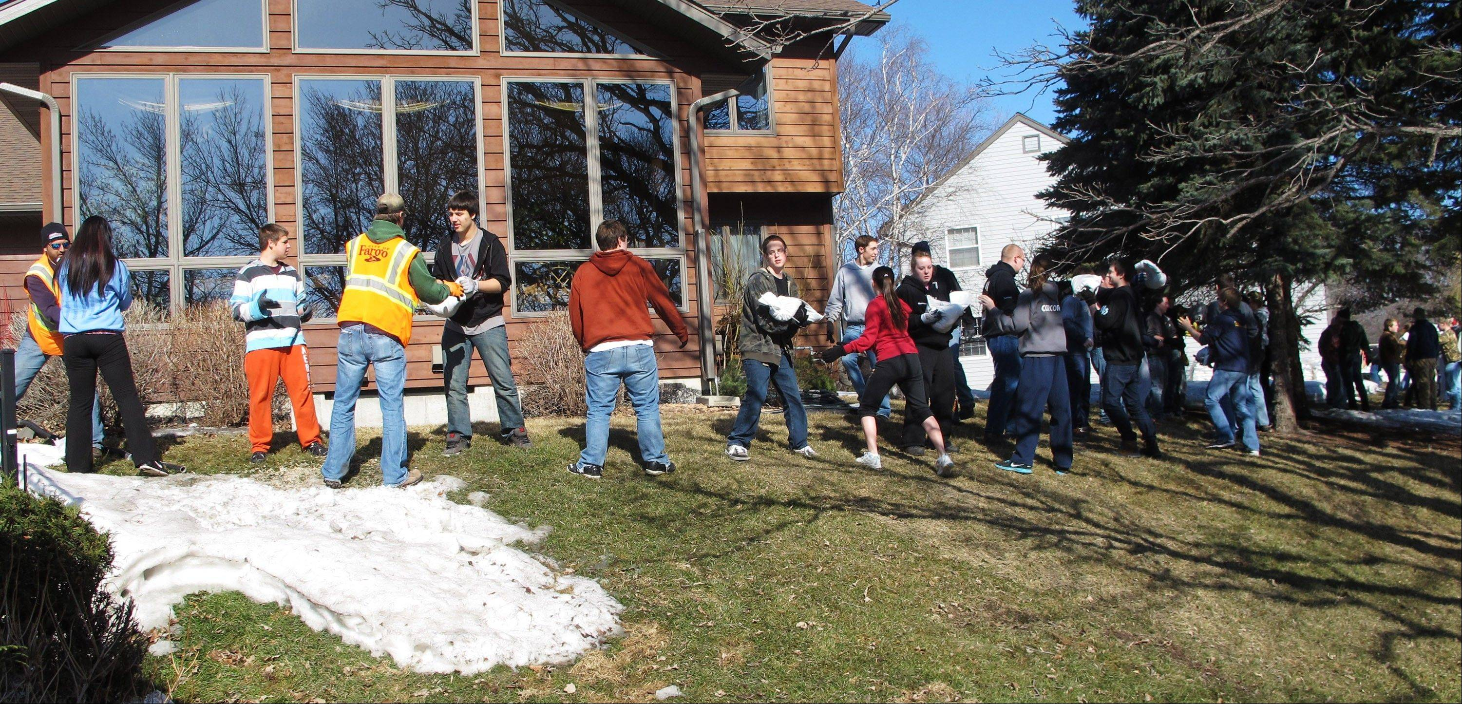 High school students toss sandbags down a line Friday in front of homes along the Red River in Fargo, N.D.