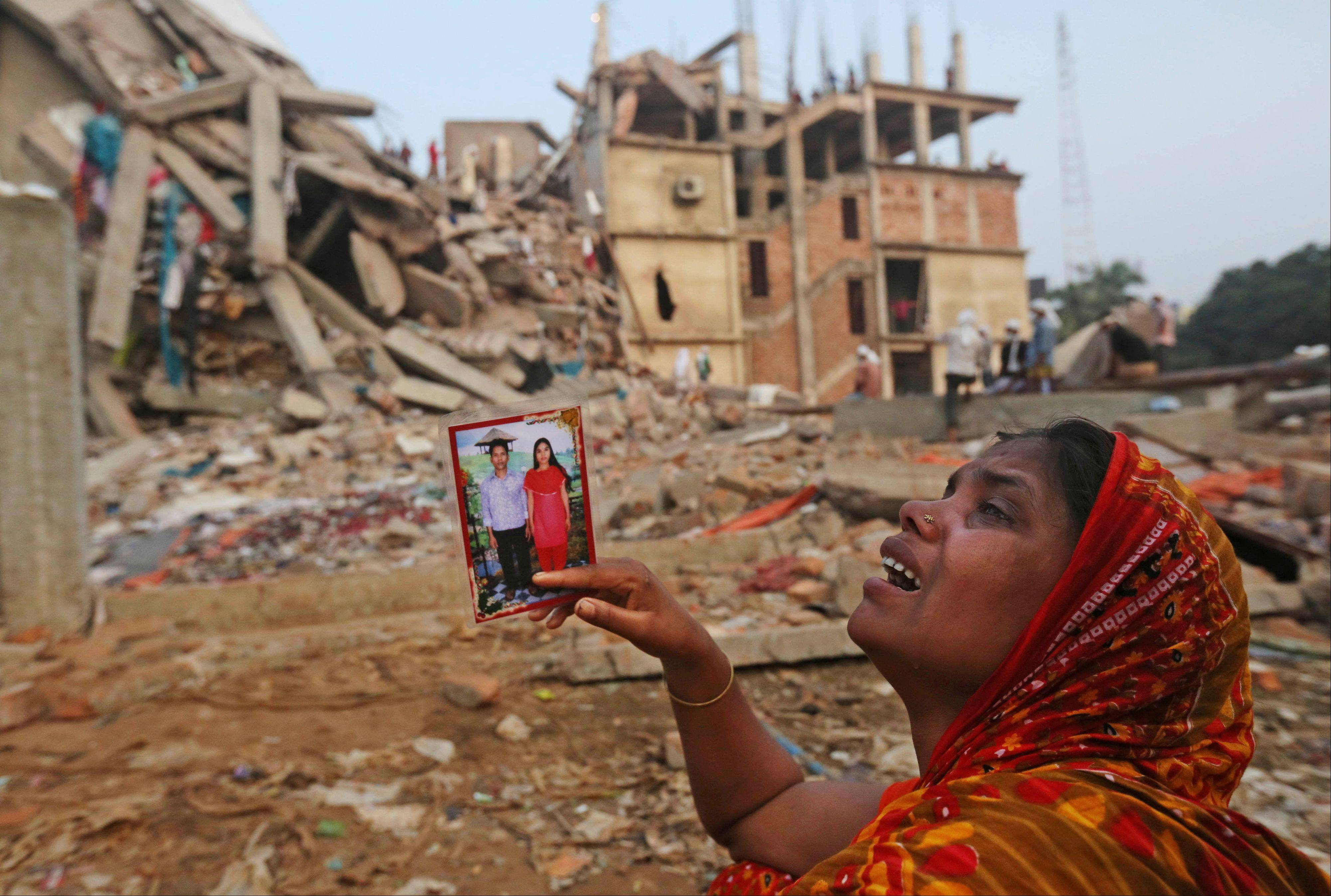 A Bangladeshi woman weeps as she holds a picture of her and her missing husband as she waits at the site of a building that collapsed Wednesday in Savar, near Dhaka, Bangladesh, Friday, April 26, 2013. The death toll reached hundreds of people as rescuers continued to search for injured and missing, after a huge section of an eight-story building that housed several garment factories splintered into a pile of concrete.