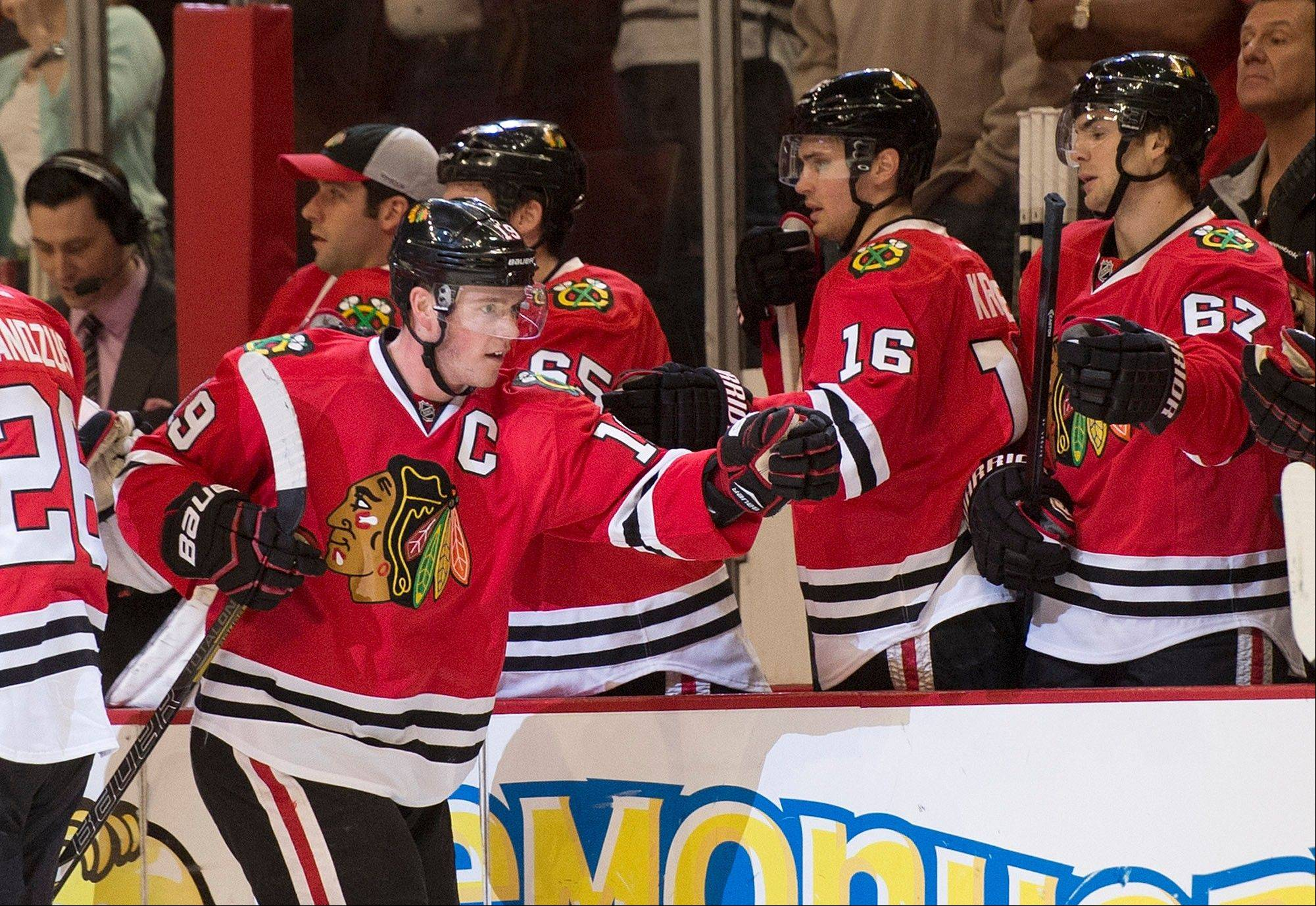 Chicago Blackhawks' Jonathan Toews, left, celebrates with his teammates after scoring a goal during the first period of an NHL hockey game against the Calgary Flames, Friday, April 26, 2013, in Chicago. (AP Photo/Brian Kersey)