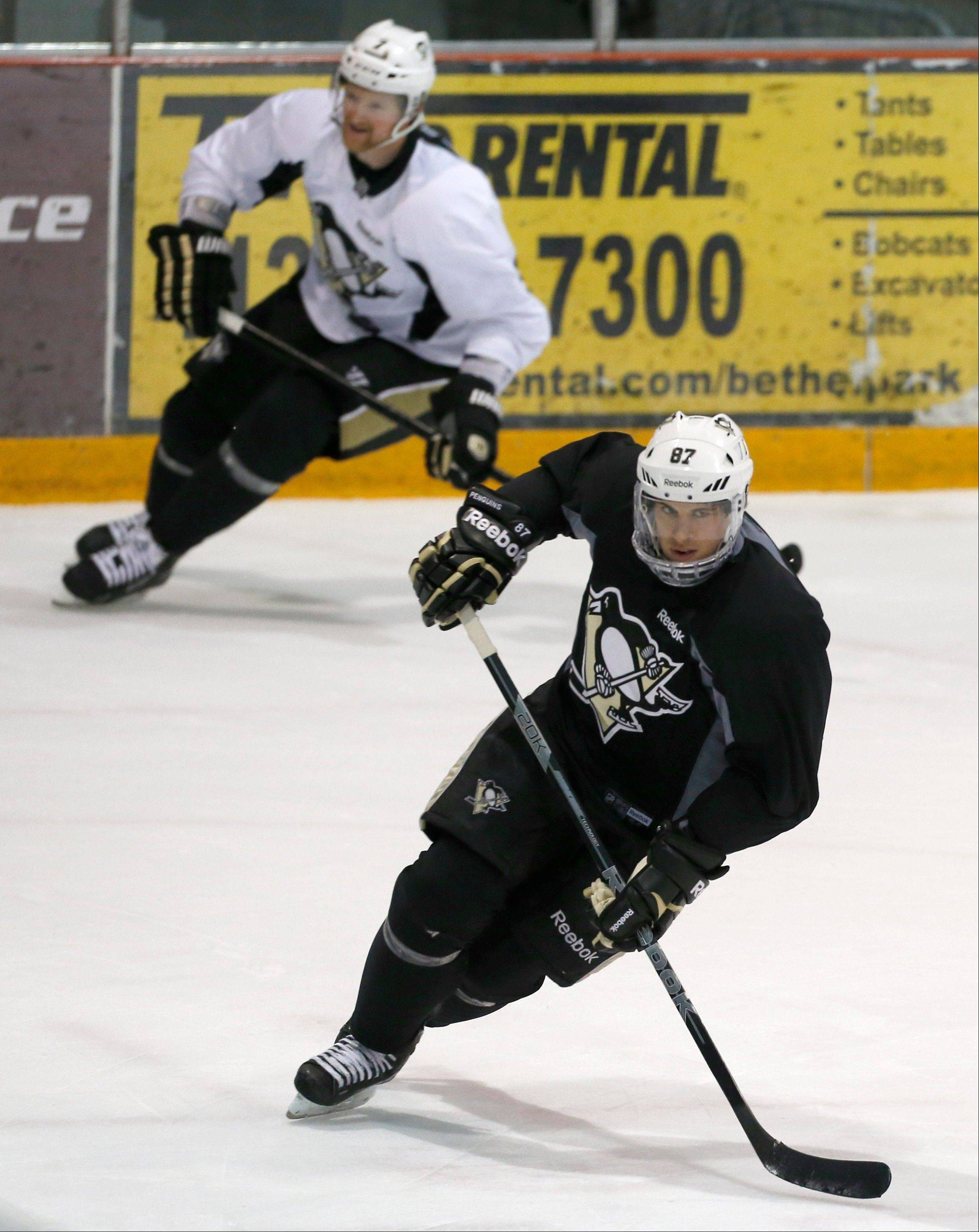 Pittsburgh Penguins Sidney Crosby, bottom, skates with Paul Martin as they participate in an NHL hockey practice on Friday, April 26, 2013, in Canonsburg, Pa. (AP Photo/Keith Srakocic)