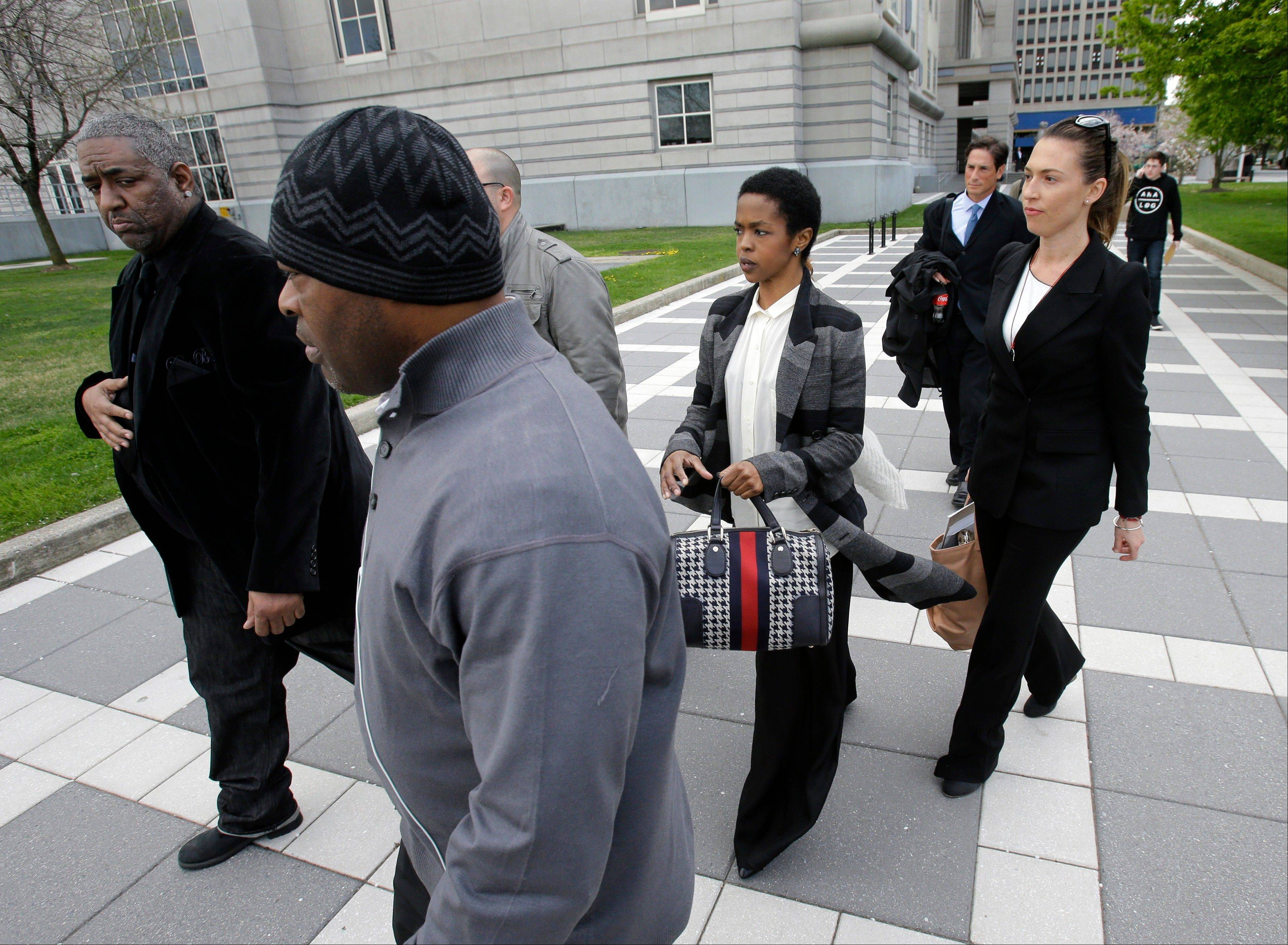 Singer Lauryn Hill, center, walks from federal court in Newark, N.J., last week after a judge postponed her tax evasion sentencing and scolded the eight-time Grammy winner for reneging on a promise to make restitution.