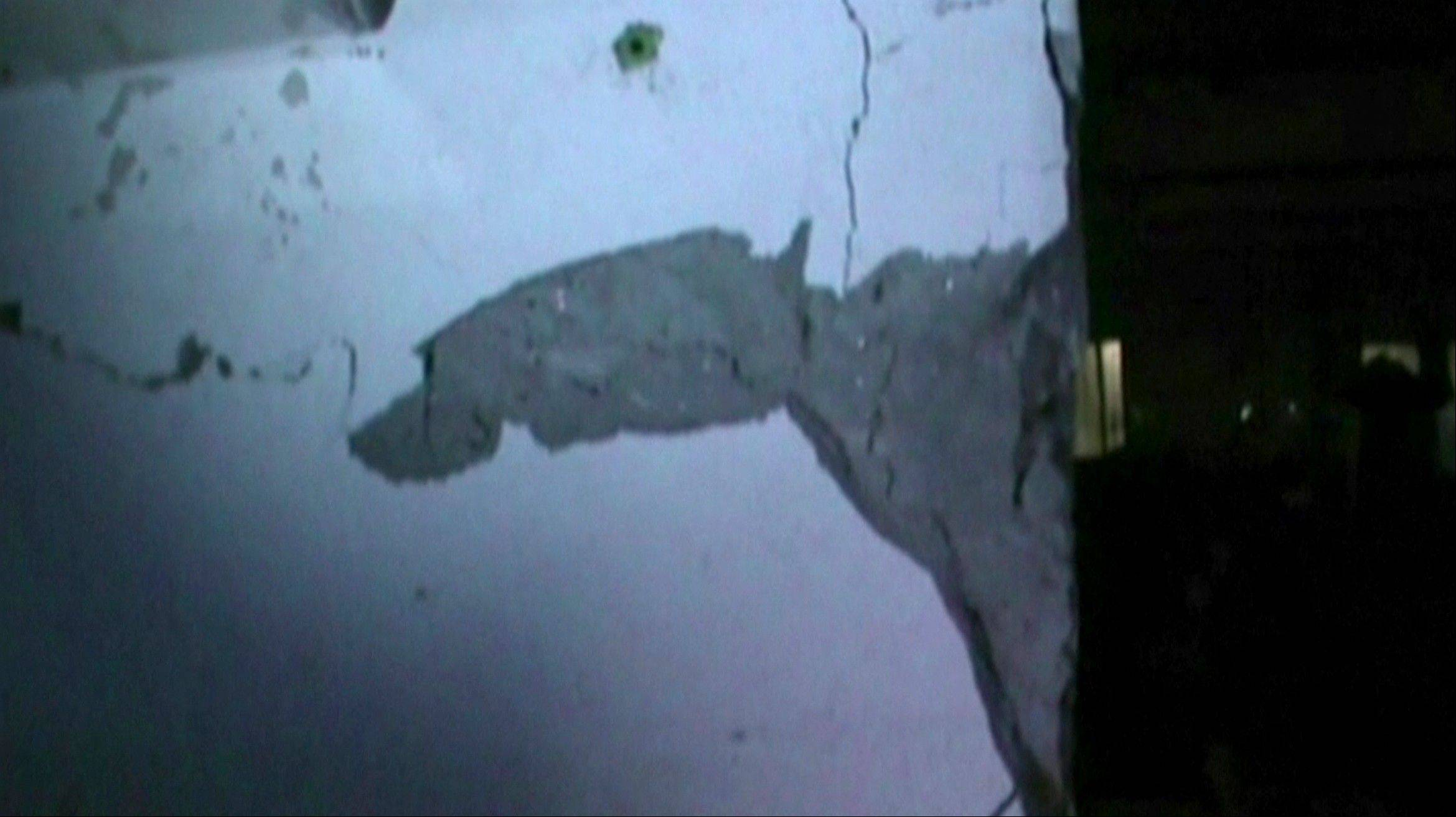 In this image made from video, cracks are seen on the wall inside Rana Plaza building, as police investigated the building Tuesday, April 23, 2013, one day before its collapse