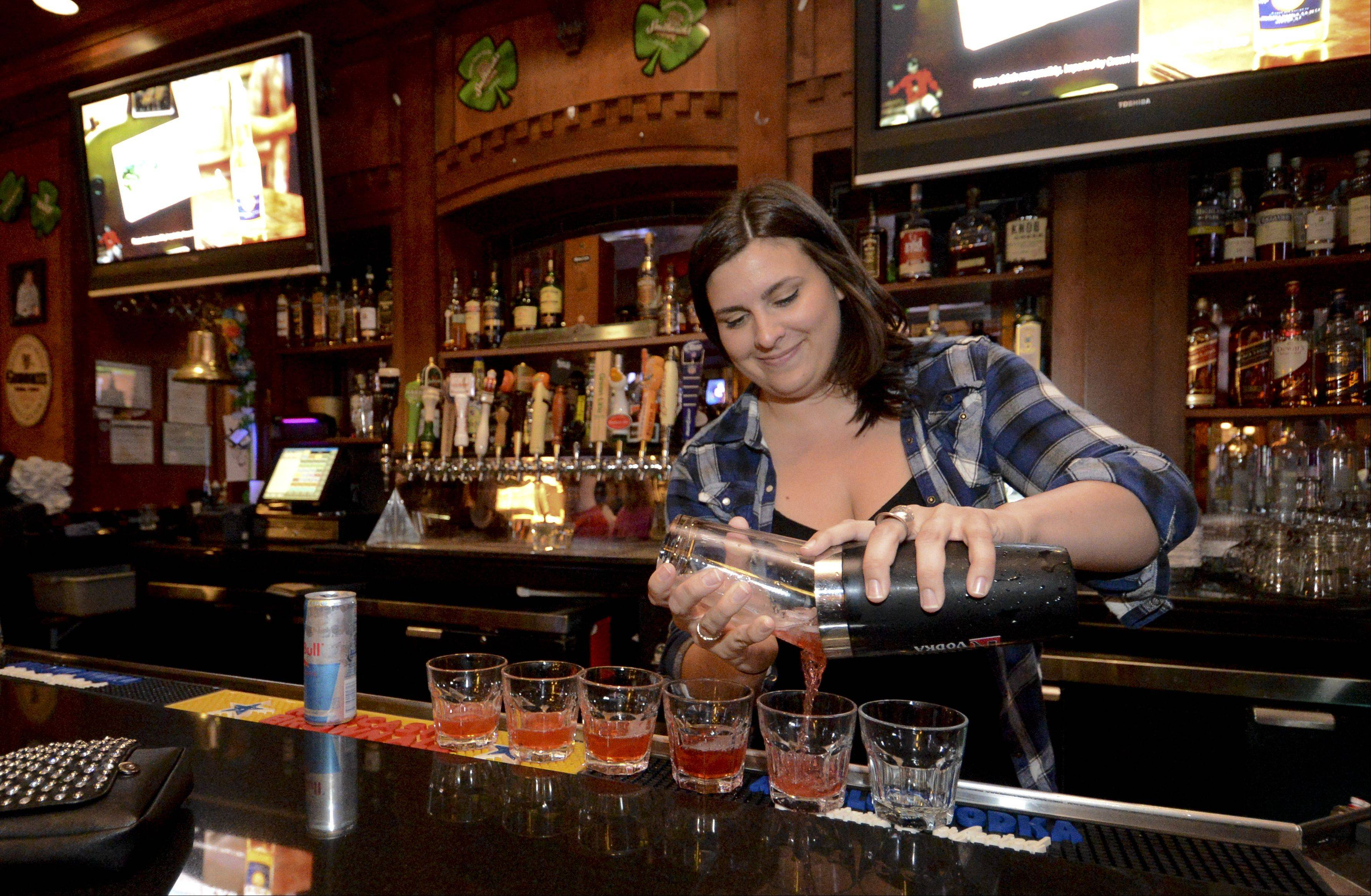 Taylor Poulos pours drinks while tending bar at Tommy Nevin's Pub in Naperville.