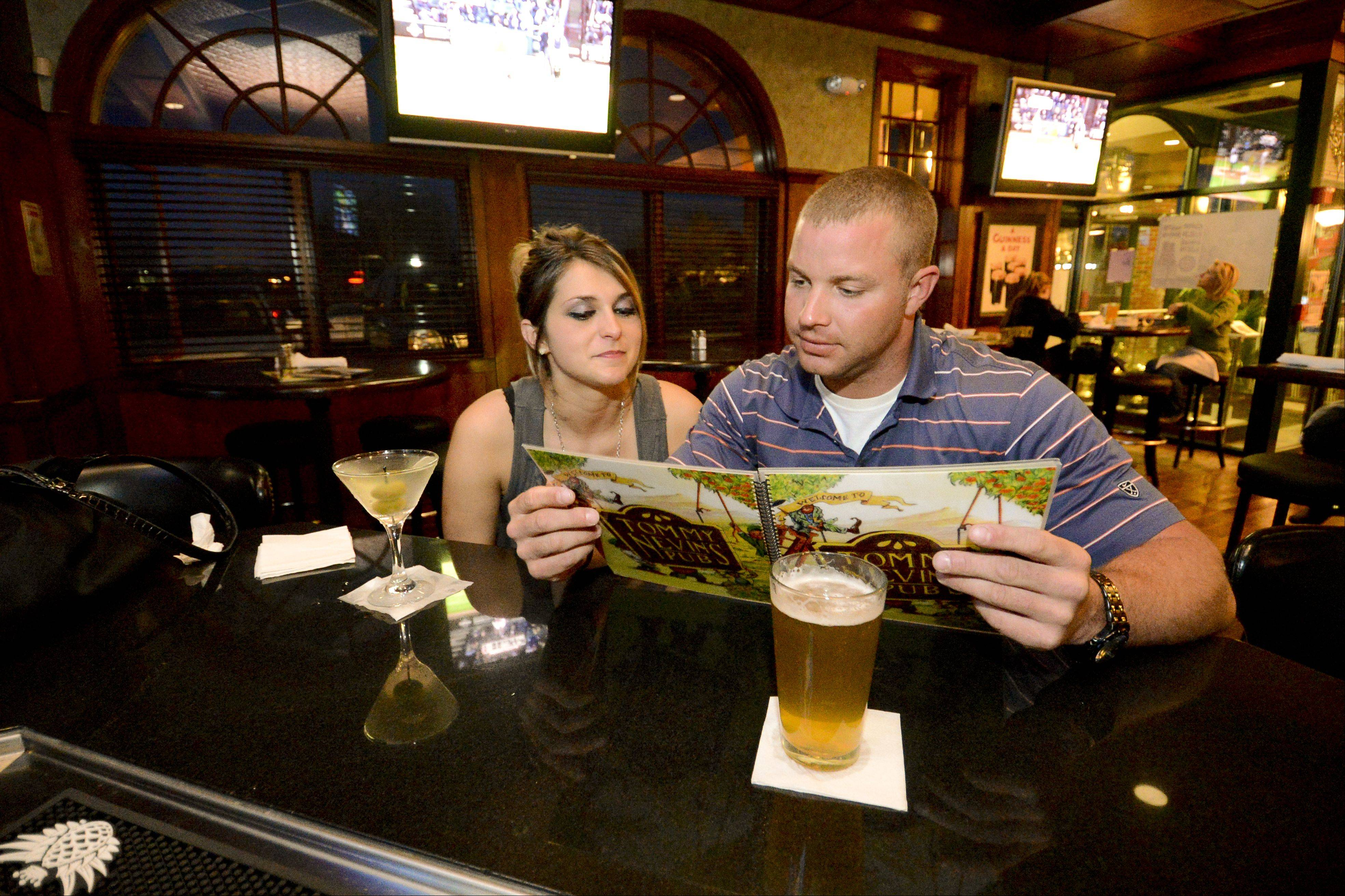 Keri Koser and Mark Swanson check out the extensive drink menu at Tommy Nevin's Pub.