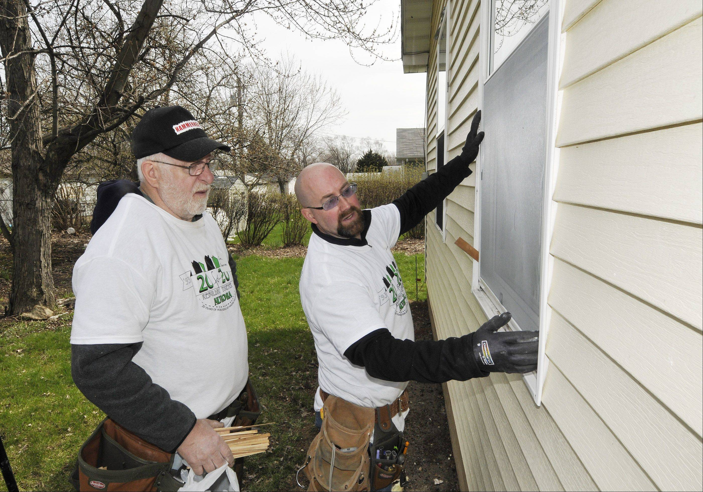 Rebuilding Together Aurora volunteers Carl Shaffer and Keith Johnson from Community Christian Church in Naperville install a new window Friday on a home in Aurora's Pattersonville neighborhood, replacing an old window pierced by a bullet. More than 800 volunteers are repairing about 20 homes Friday and Saturday during Rebuilding Together Aurora's 20th annual April home repair event.