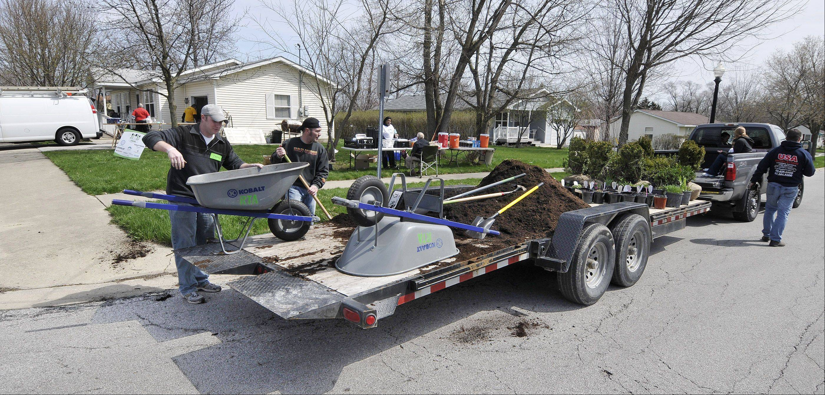 Employees from Chad Ford's Snow Removal and Concrete in Aurora donated their time and trucks Friday to deliver mulch and landscaping materials to locations in the near east side Pattersonville neighborhood where Rebuilding Together Aurora volunteers were rehabbing homes during the 20th annual April rebuilding event.