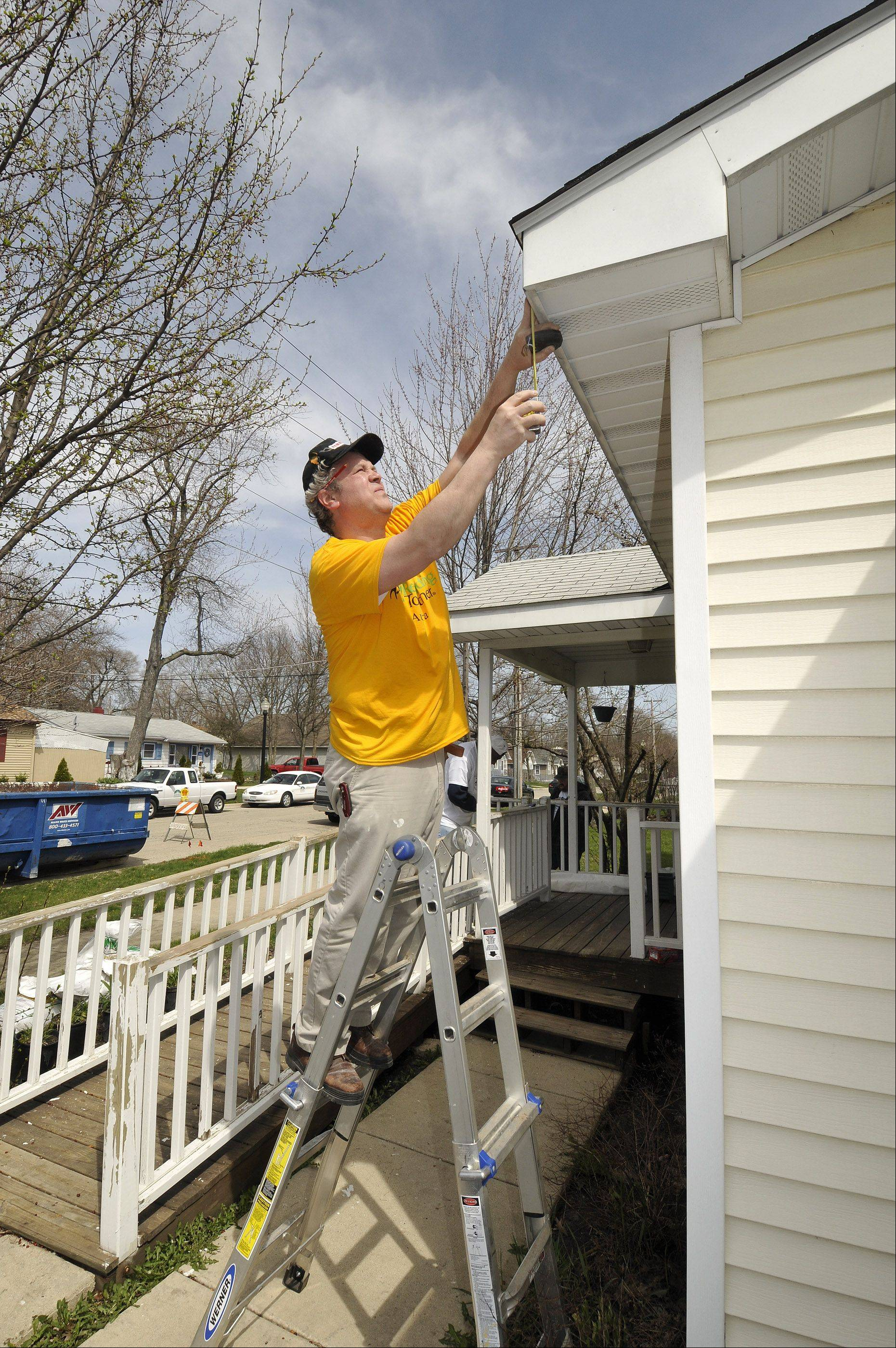 Warren Seidel from Naperville's Community Christian Church measures for a new gutter Friday at a home in Aurora's Pattersonville neighborhood as a volunteer group from his church participates in Rebuilding Together Aurora's 20th annual April home repair event.