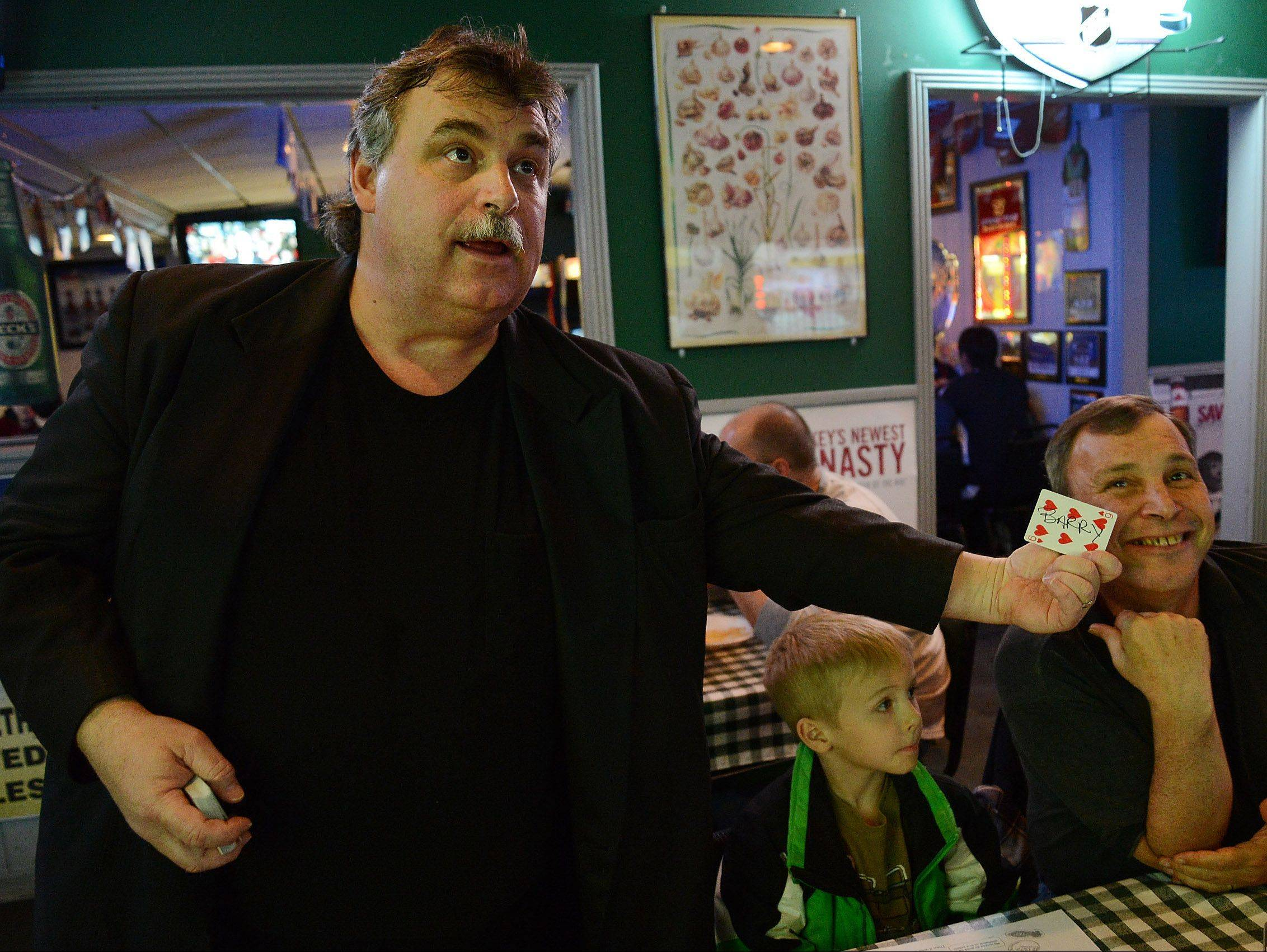 Magician Mark Doetsch clowns around with patrons while performing magic at Gators in Palatine.