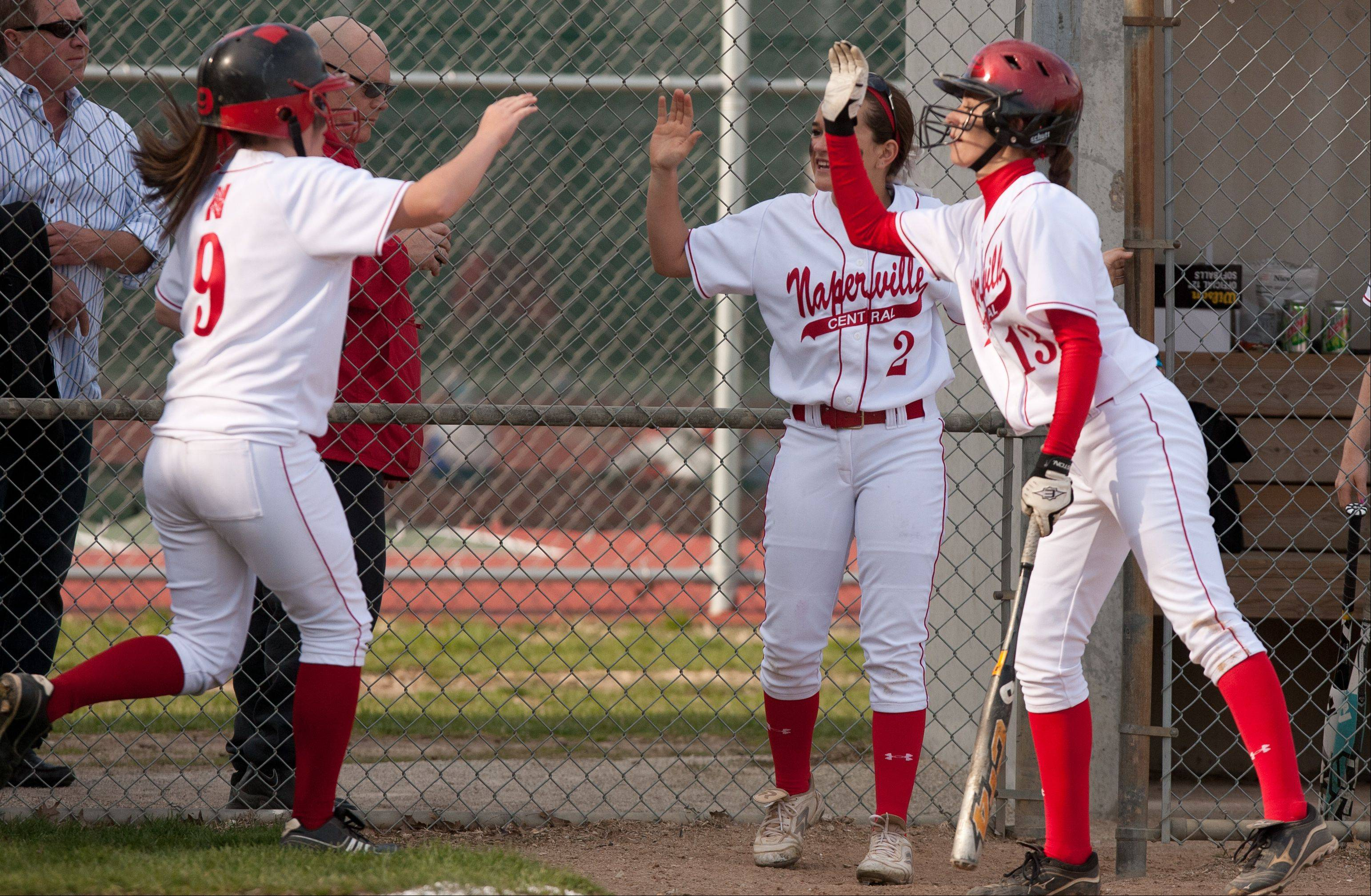 Daniel White/dwhite@dailyherald.comNaperville Central's Emily George, left, high fives Katie Lamich (2) and Courtney Giebel (13) after scoring against Naperville North, during girls softball action.