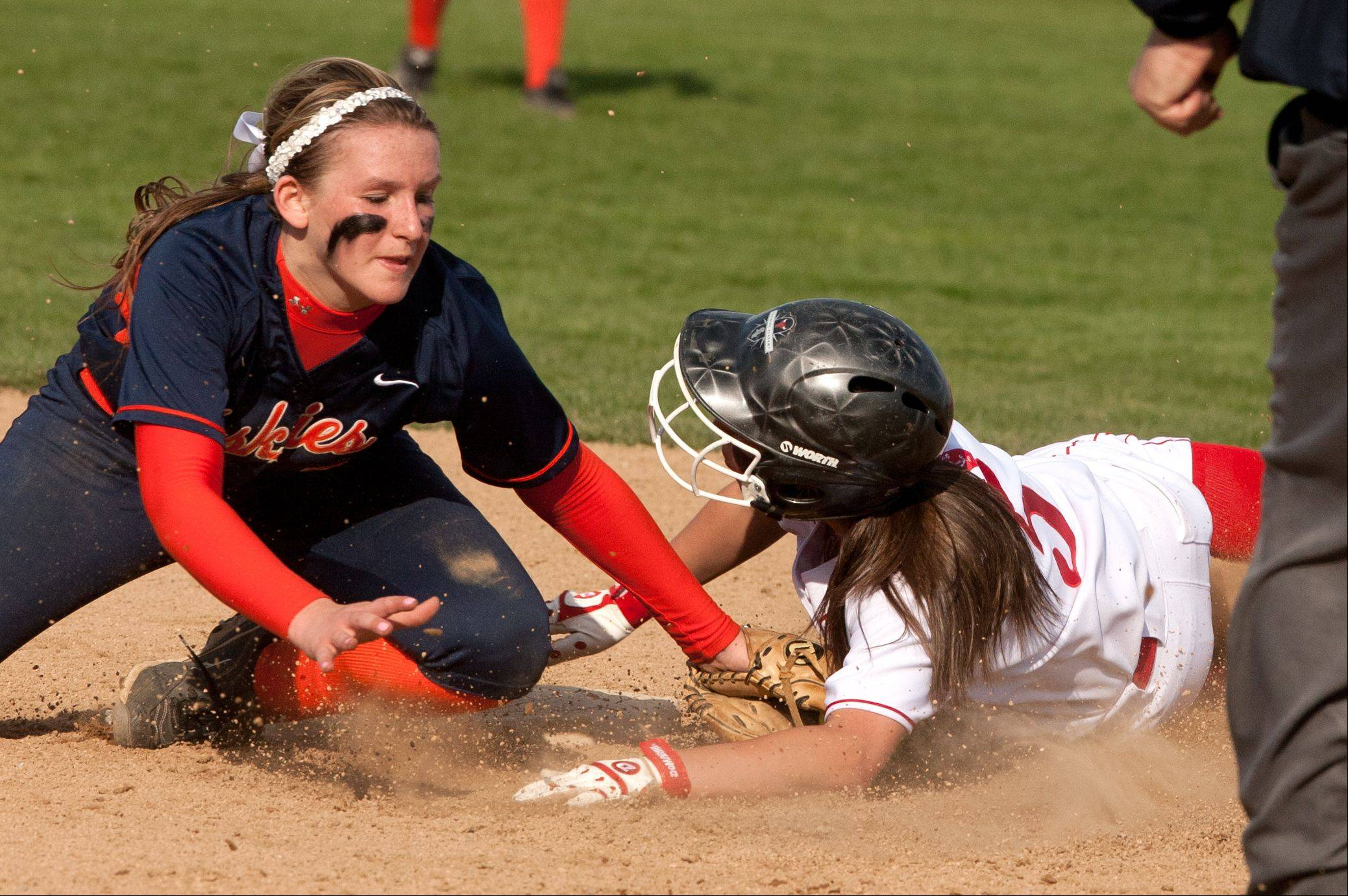 Daniel White/dwhite@dailyherald.comNaperville North's Alexis Solak, left, applies the tag to Naperville Central's Lindsey Gonzalez, who was called safe, during girls softball action.