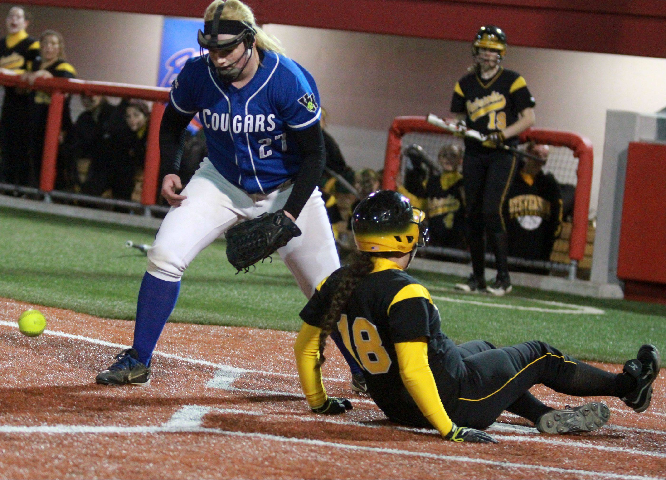 Stevenson's Abby O'Connor slides safe into home plate as Vernon Hills' pitcher Jenn Claussen covers the plate after throwing a wild pitch in the fifth-inning at The Ballpark at Rosemont on Friday.