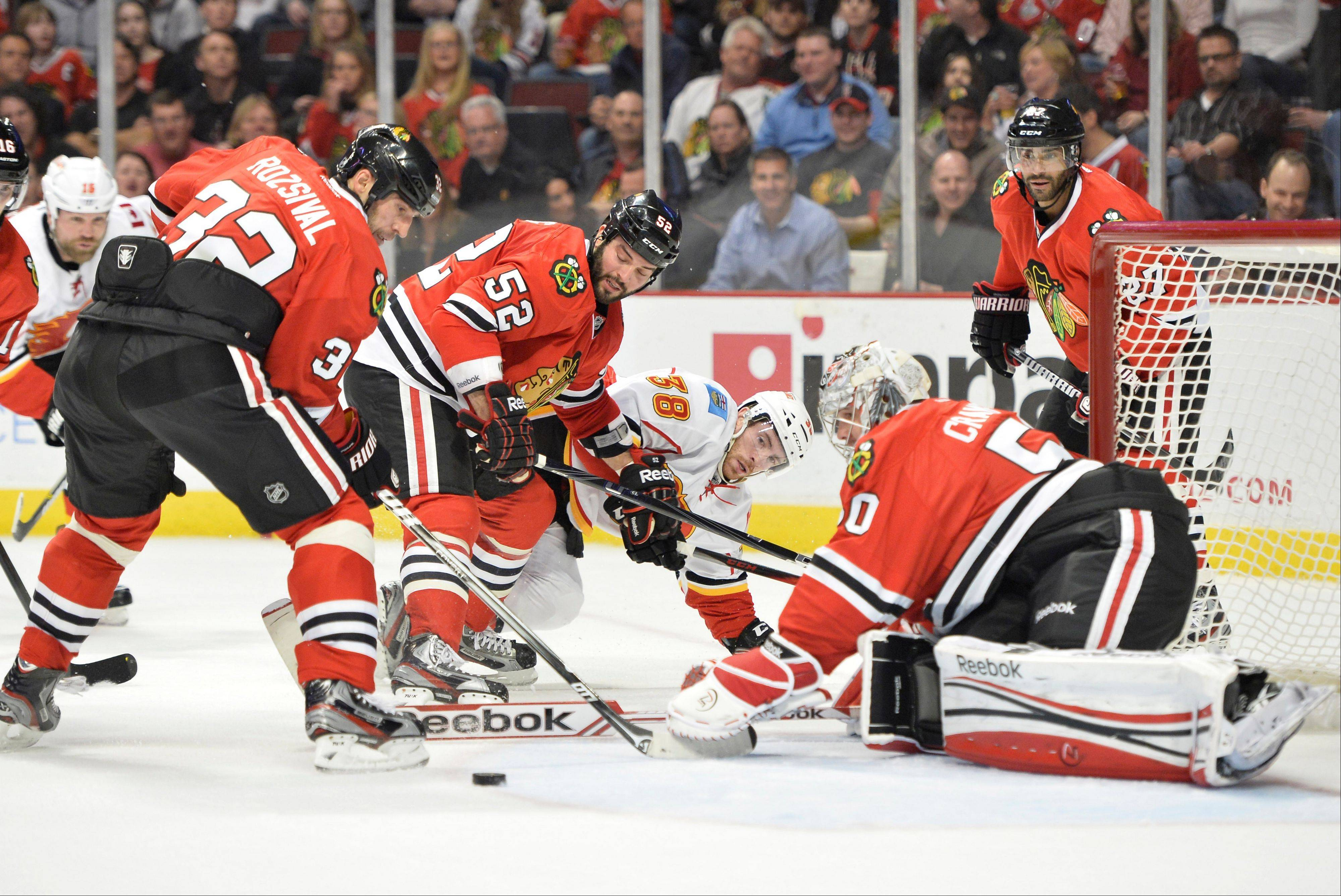 Michal Rozsival, left, of the Czech Republic, Brandon Bollig (52) and goalie Corey Crawford defend the net as Calgary's Ben Street, center, tries to score during the first period Friday.