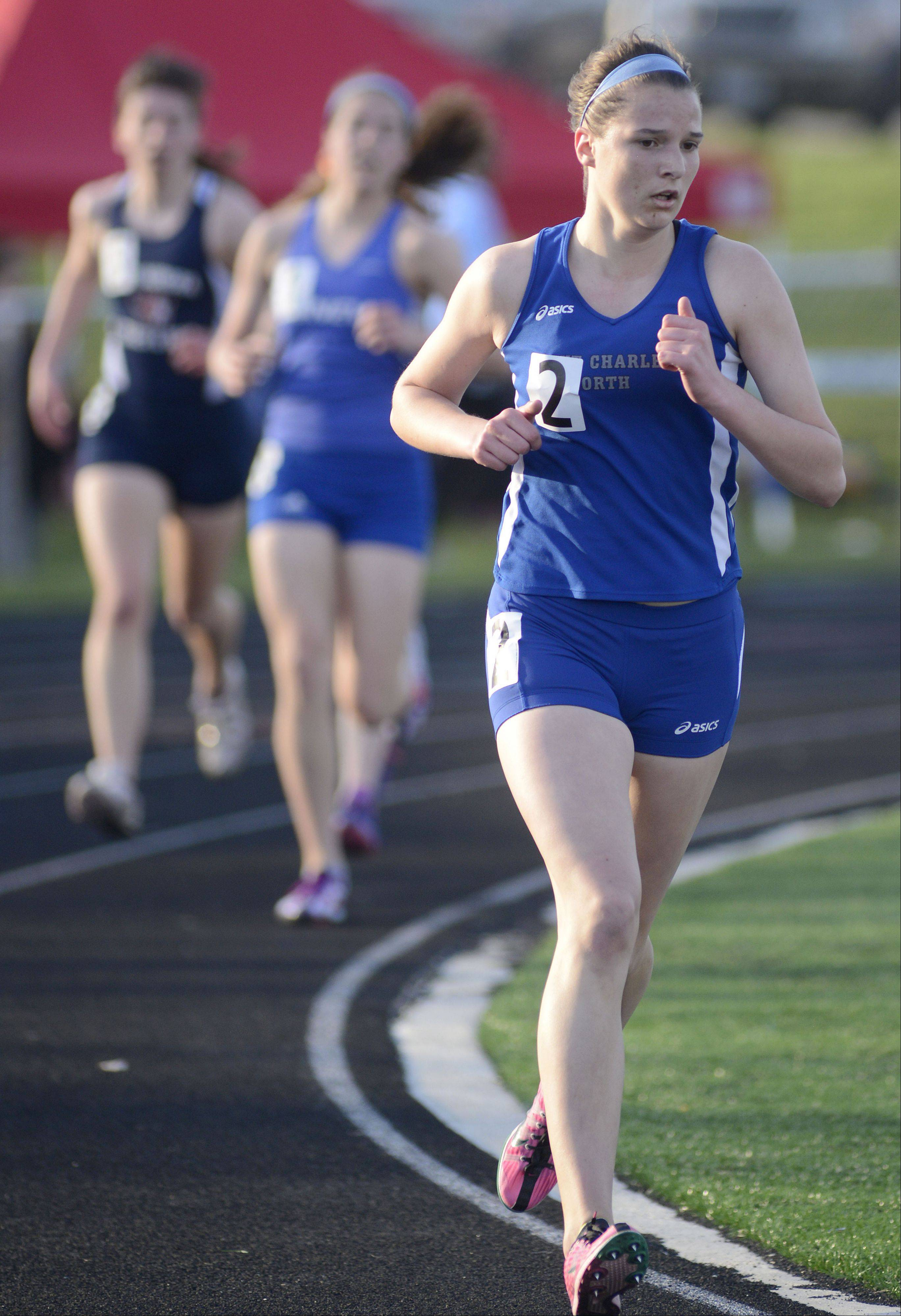 St. Charles North's Ashley England leads the 3200 meter run and takes first place at the Kane County Invitational track in Geneva meet on Friday, April 26.