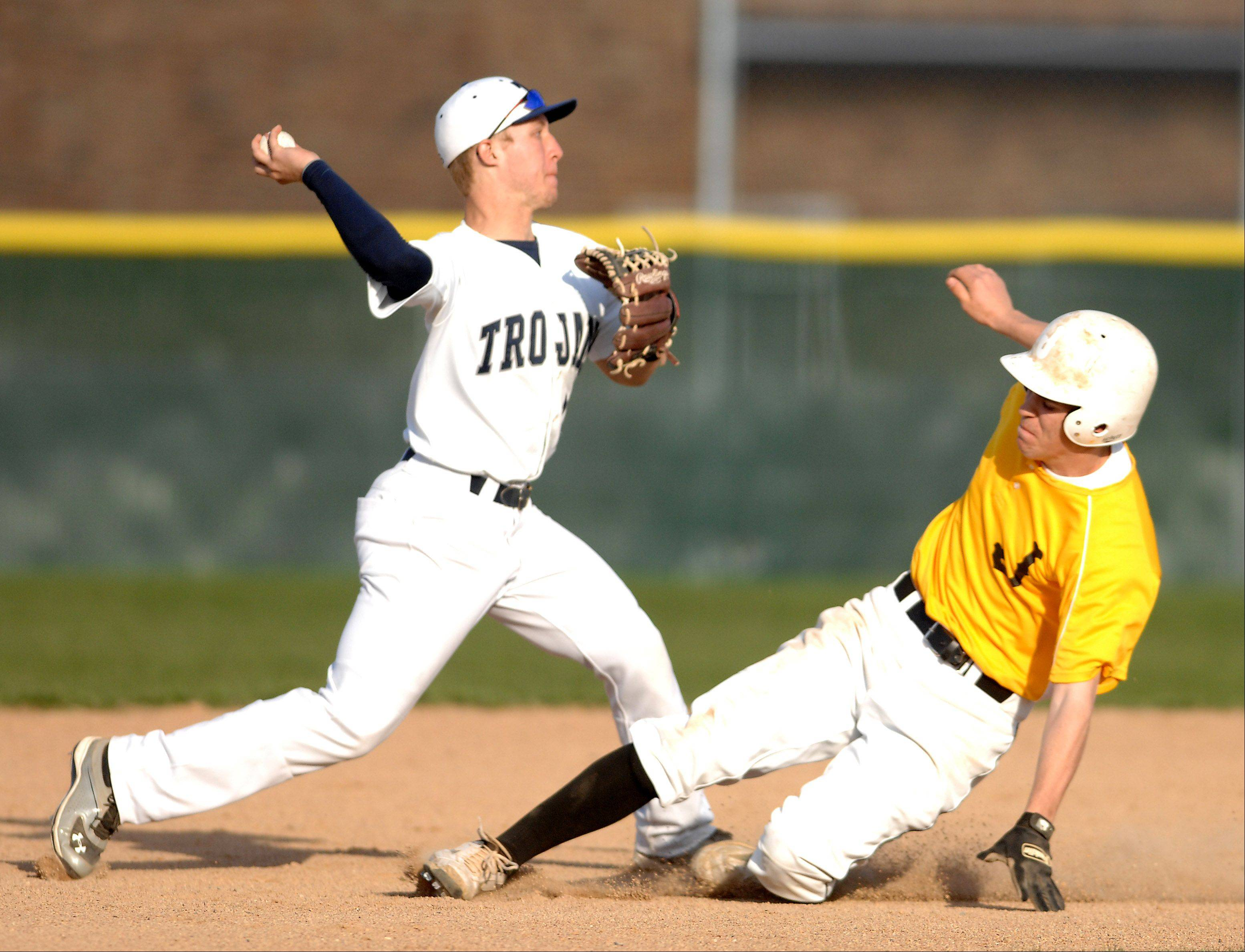 Cary-Grove's Jeremy Vasquez turns a double play as Matt Hickey of Jacobs bears down on him during Friday's game in Cary.