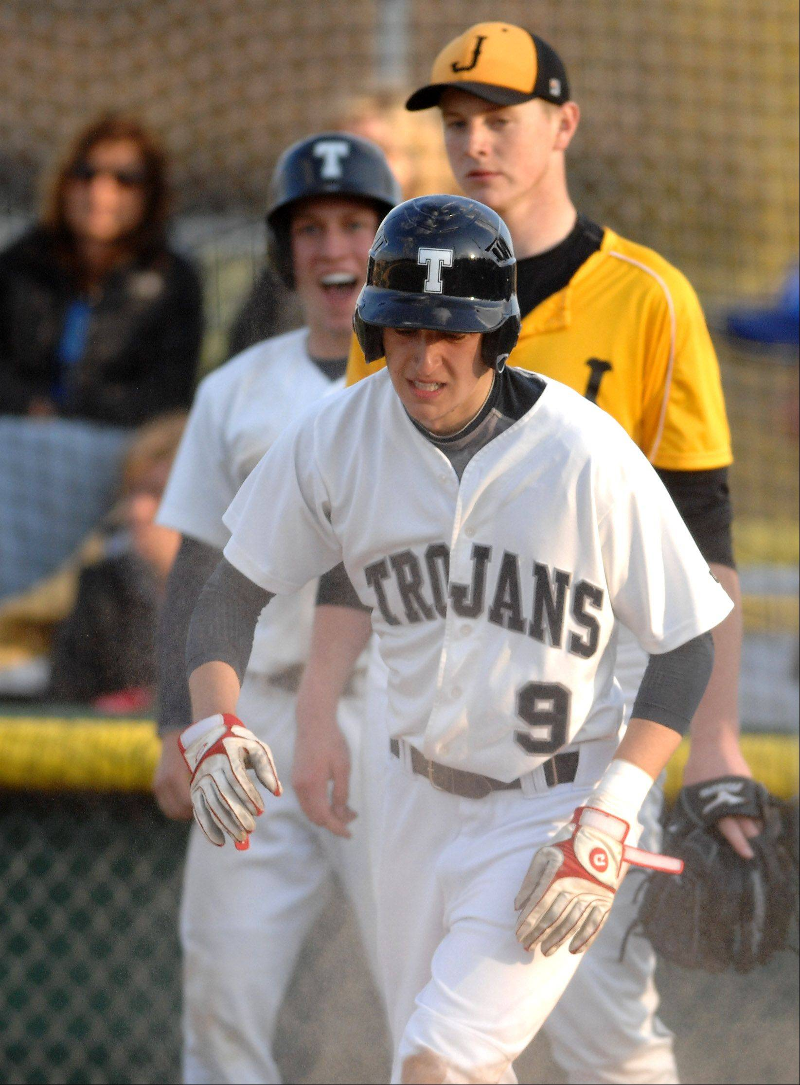Both ends of the emotional spectrum are seen behind Cary-Grove's Dean Christakes as he pops up after sliding in to home to give the Trojans the lead over Jacobs during Friday's game in Cary.