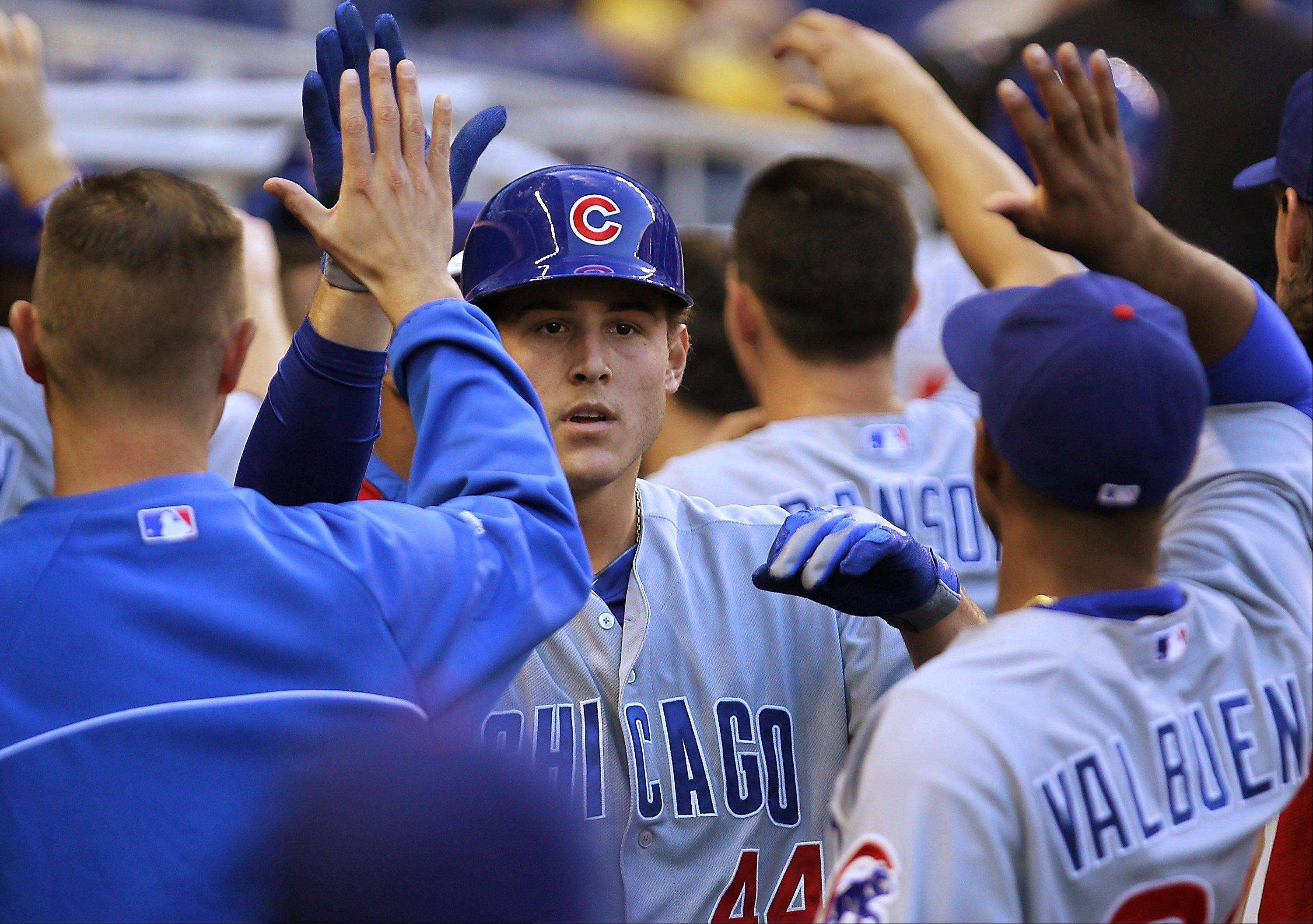 Chicago Cubs first baseman Anthony Rizzo, center, is congratulate by teammates after hit two-run home run during the first inning of their baseball game against the Miami Marlins in Miami on Friday, April 26, 2013. (AP Photo/El Nuevo Herald, David Santiago) MAGS OUT.