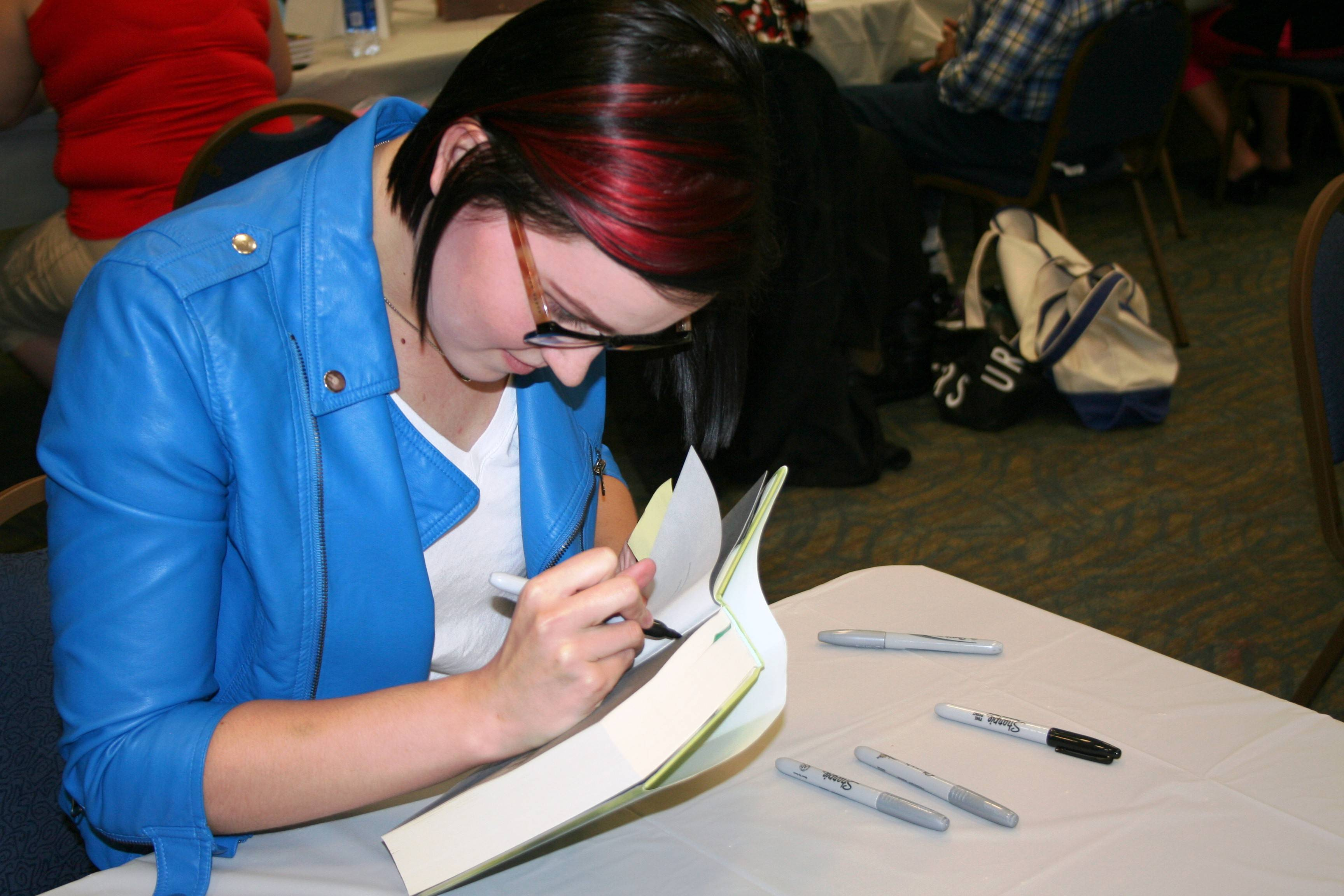 "Guest author Veronica Roth (""Divergent"") signs an autograph at the Aurora Public Library's Catch a Bunch of Authors Fair in September, 2012 at the Prisco Community Center in Aurora."