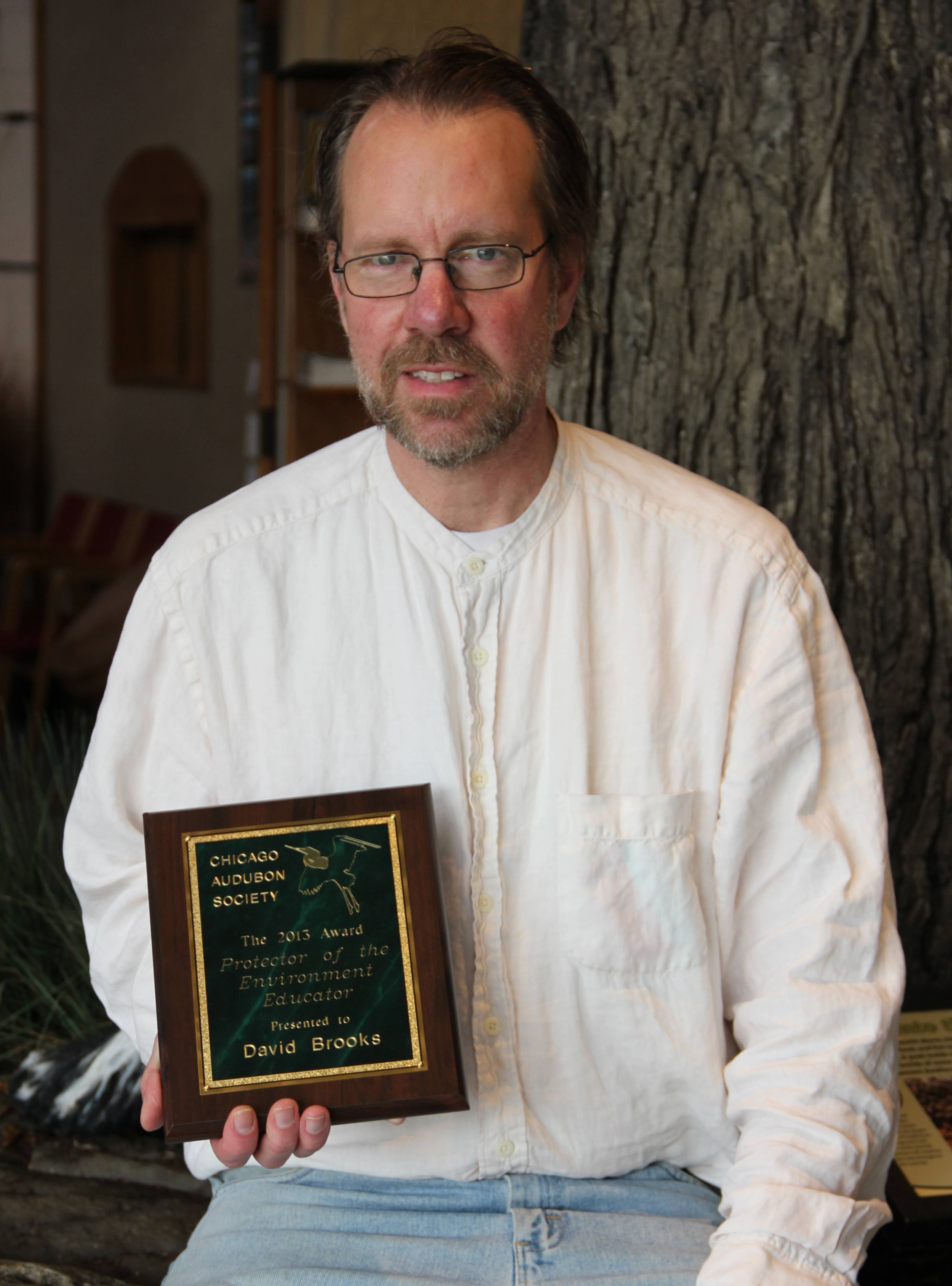 Dave Brooks, manager of conservation services, smiles with his award from the Chicago Audubon Society.