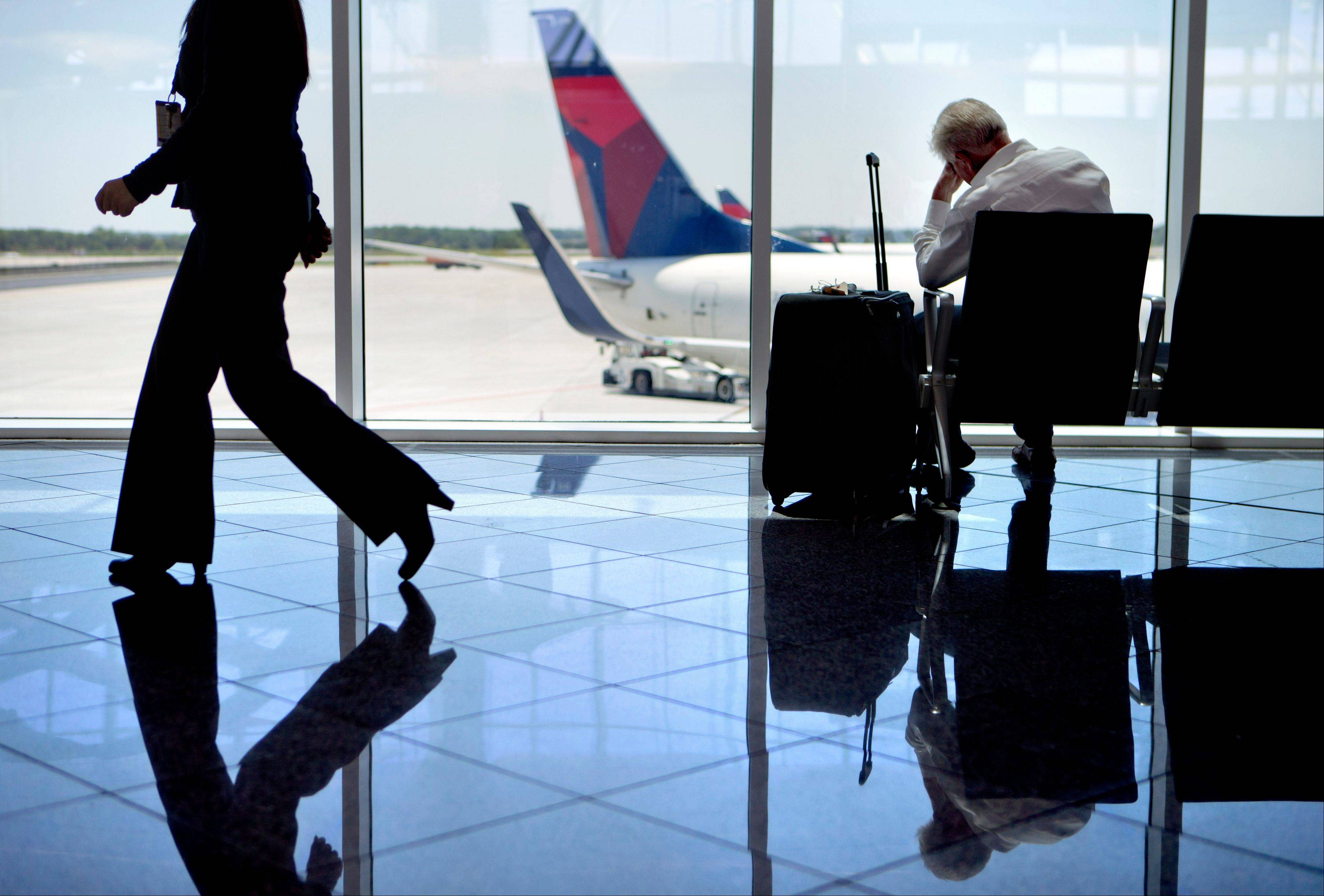A passenger sits in the international terminal at Hartsfield-Jackson airport in Atlanta.