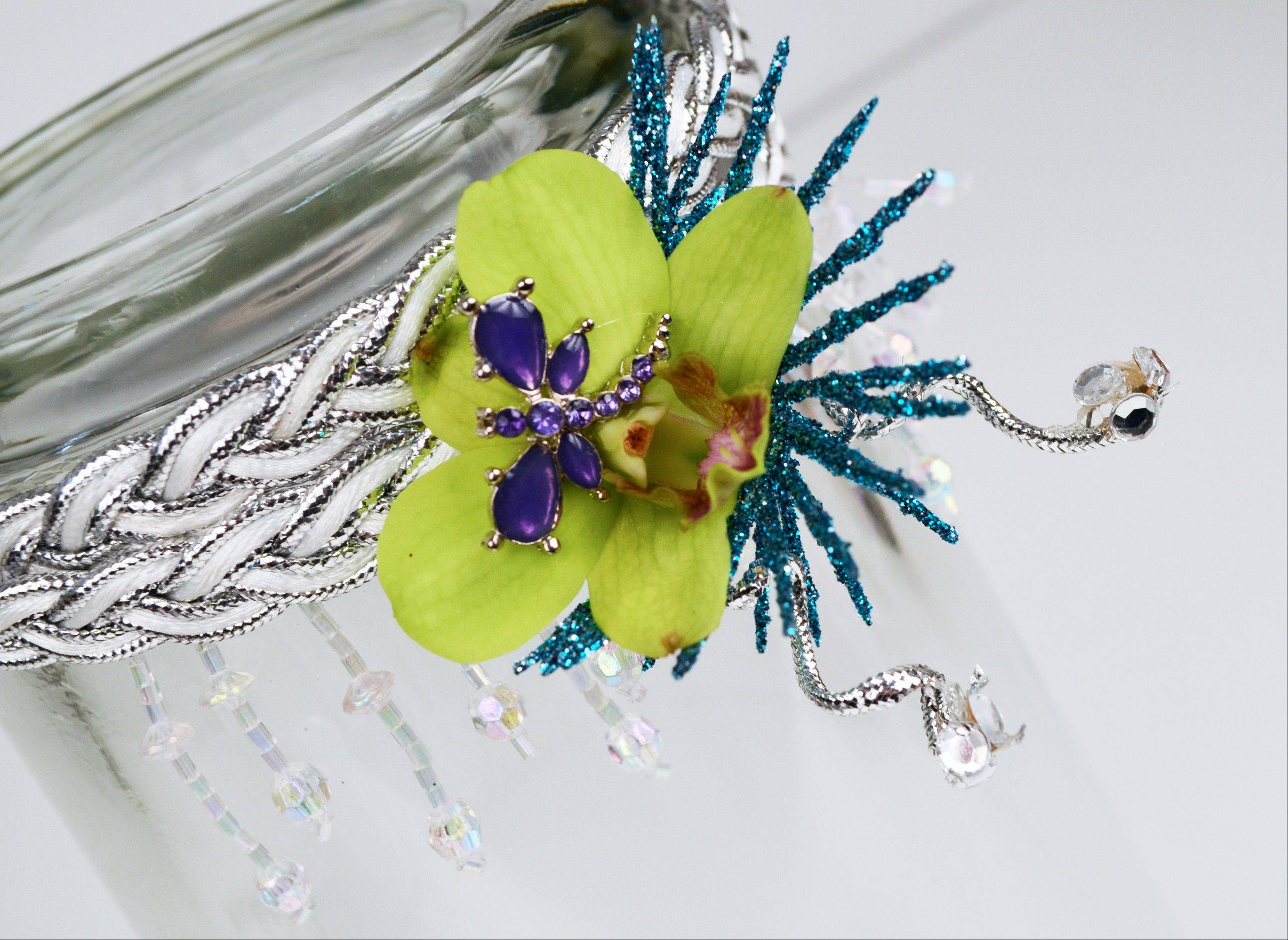 A floral headband is made with a green orchid, dragonfly pin, dangling beads, blue glittered leaves, silver accent ribbon, rhinestones and a braided silver and white headband.