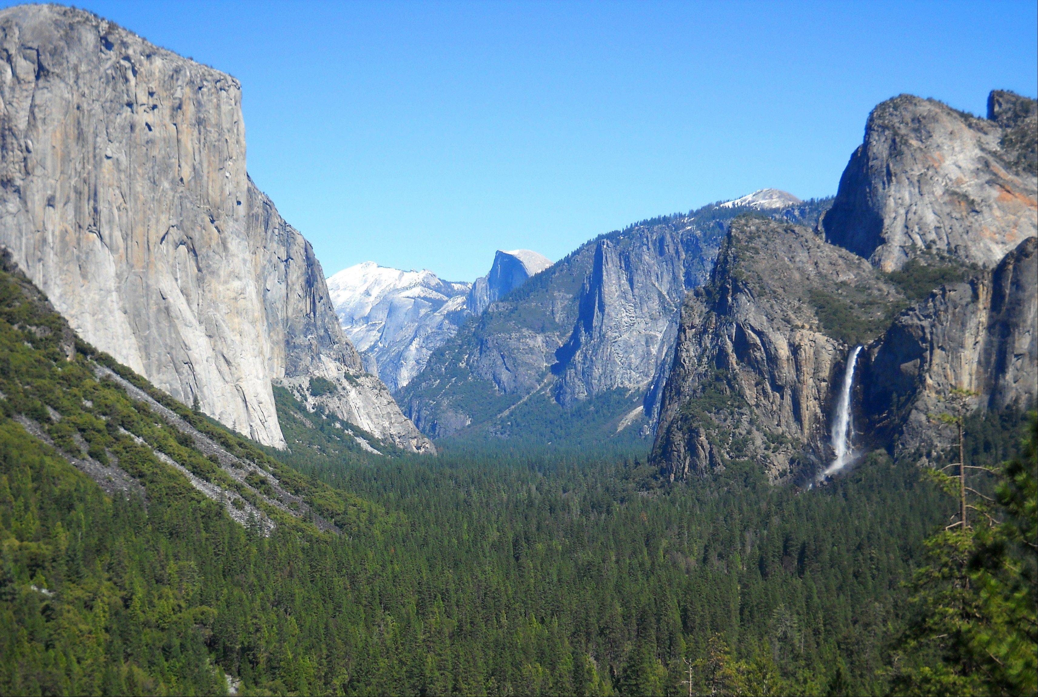 Yosemite Valley as seen from Tunnel View with three of Yosemite National Park's best-known natural attractions: The El Capitan summit on the left, the granite peak known as Half Dome in the distant center, and Bridalveil Fall on the right.