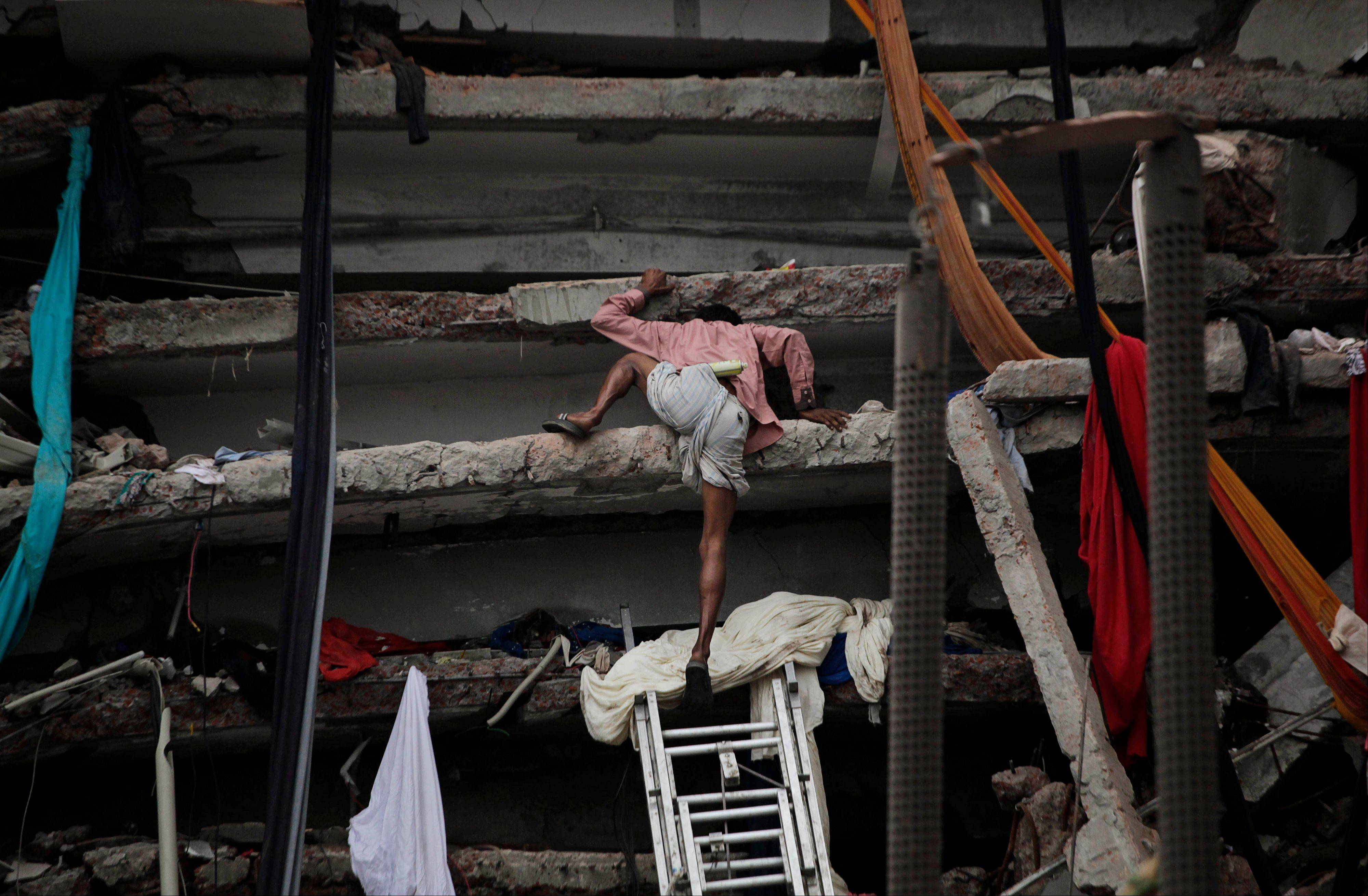 A Bangladeshi civilian rescue volunteer climbs a section of a building Saturday that collapsed Wednesday in Savar, near Dhaka, Bangladesh.