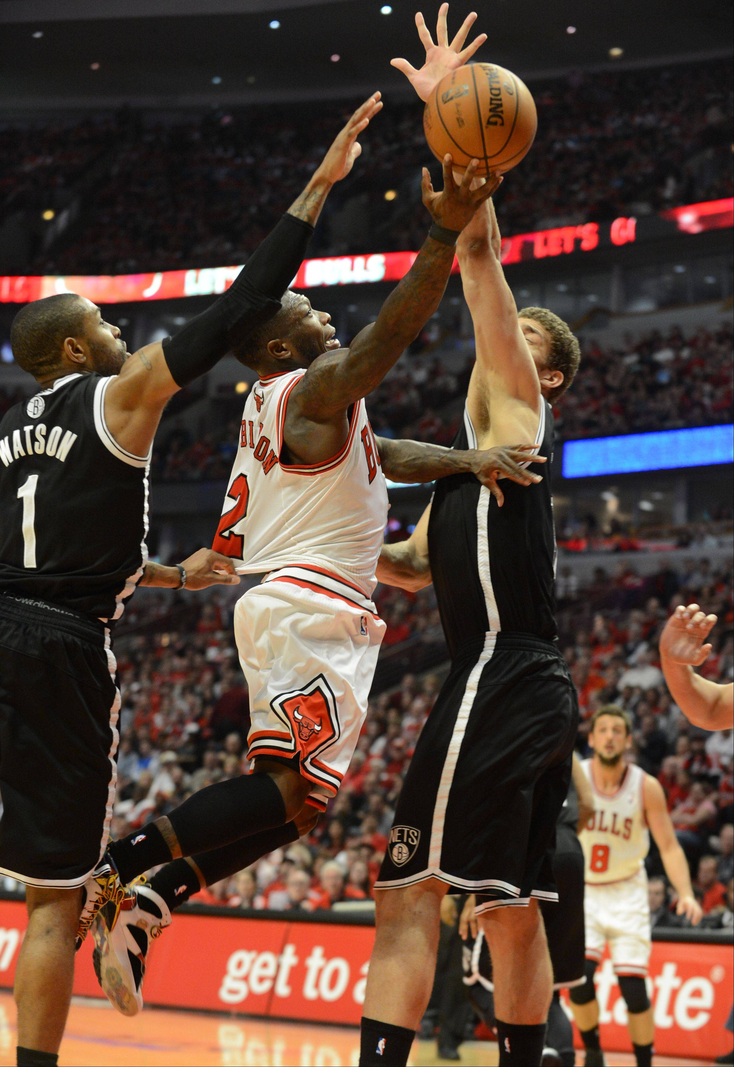 Nate Robinson goes for the basket between Brooklyn�s C.J. Watson, left, and Brook Lopez, right, Saturday during Game 4 of the first-round playoff game against the Brooklyn Nets at the United Center. The Bulls won 142-134 in triple overtime.