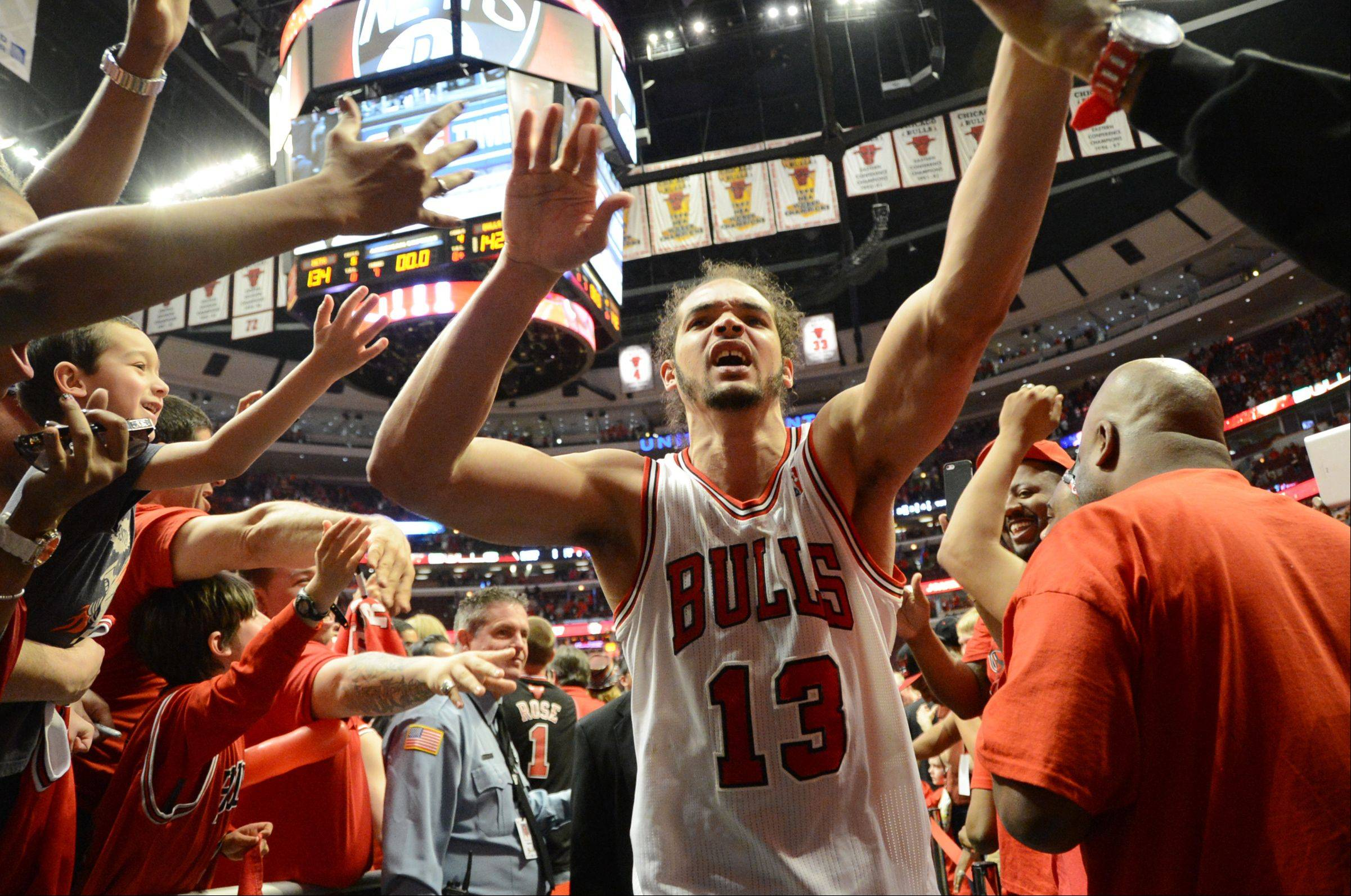 Joakim Noah is greeted by fans as he comes off the court Saturday during game 4 of the first round playoff game against the Brooklyn Nets at the United Center. The Bulls won in triple overtime 142-134.