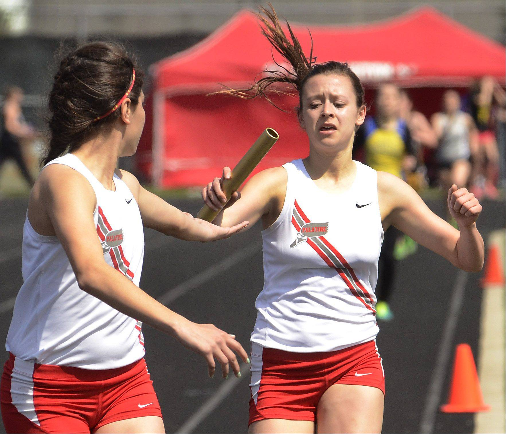 Palatine�s Tess Wasowicz, right, hands off to Lorena Soriaba on the first leg of the distance medley at the Palatine Relays on Saturday. Palatine won the event in 12:31.48.