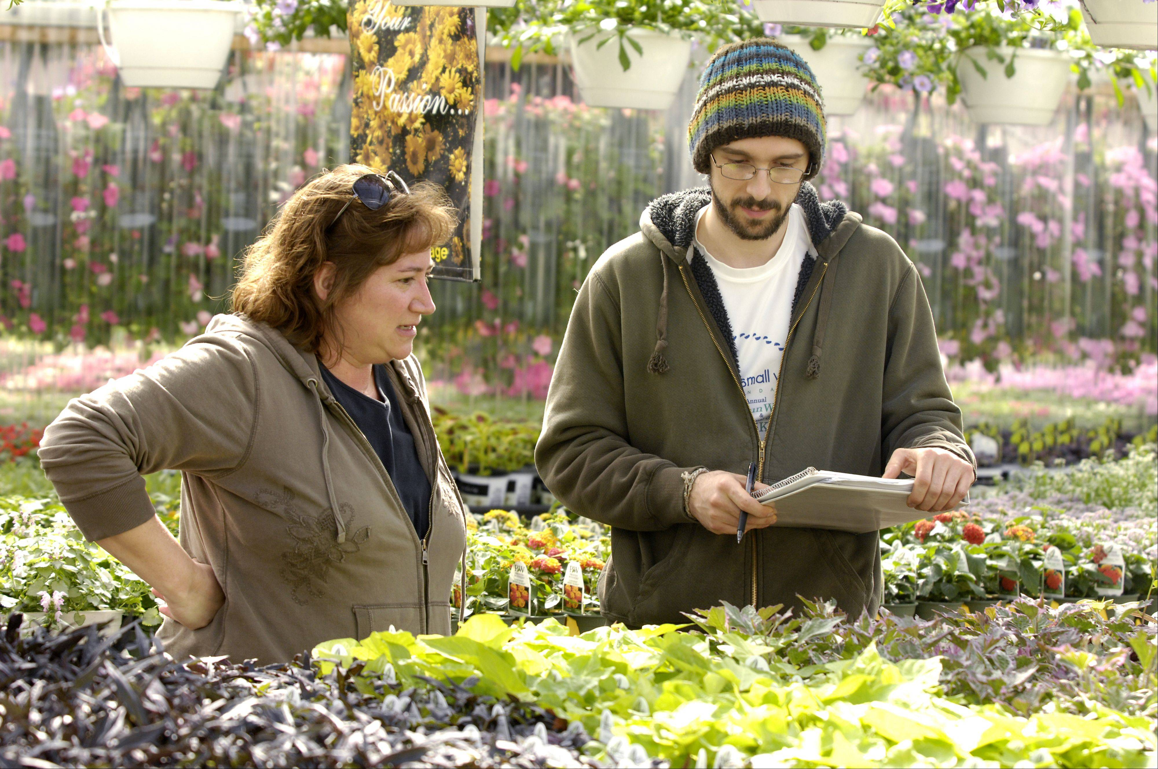 Amy Hull College of DuPage greenhouse supervisor and adjunct faculty member works with horticulture student Warren Kahtib, in the college's greenhouse.