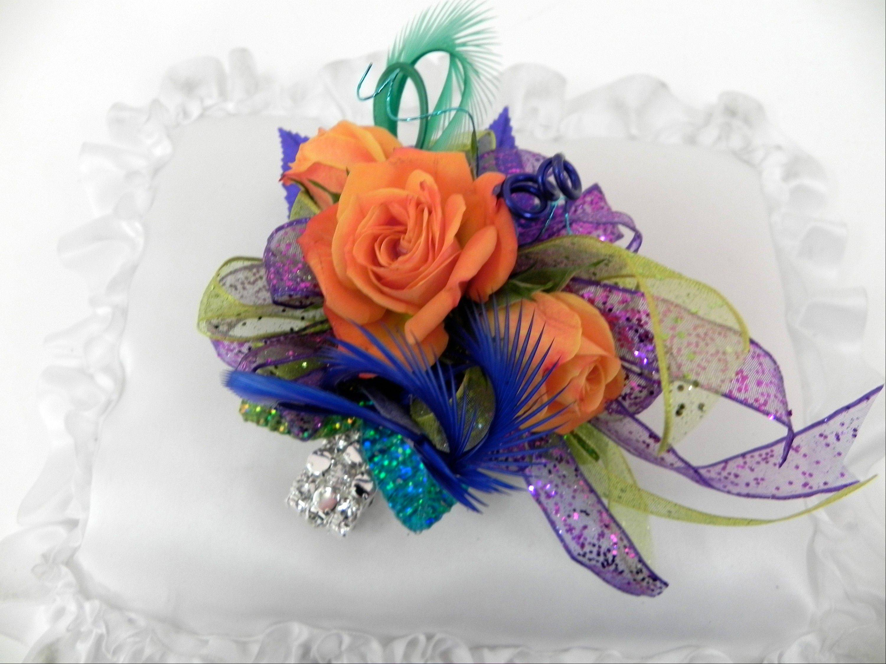 The Pandora corsage is designed with three orange sweetheart roses, purple and lime green glitter ribbon, blue and sea foam green feathers, blue, turquoise and green silk leaves, and blue and green wire on a Fitz Design Bracelet called RockStar Dazzle.
