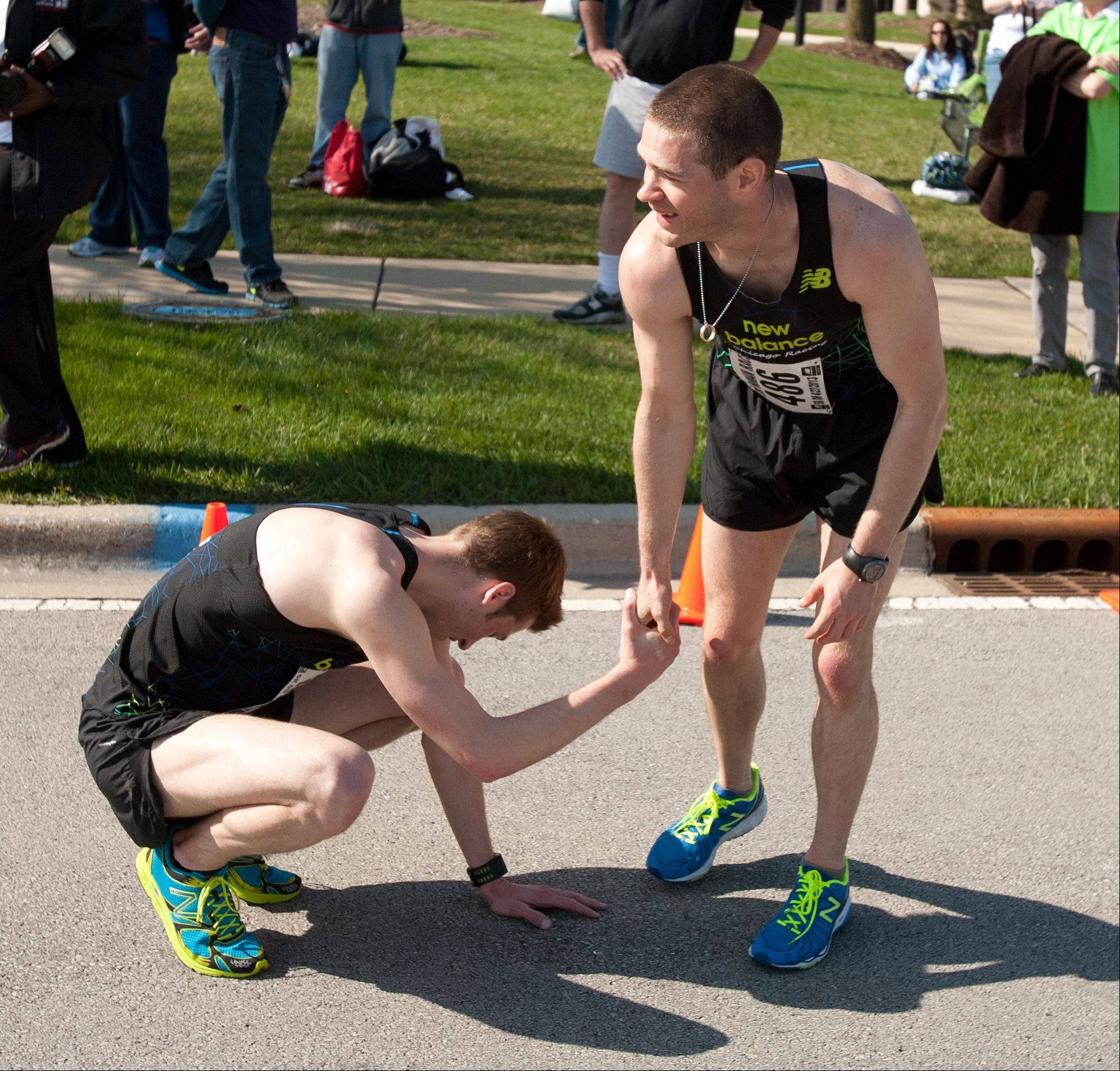 Patrick Austin of Plattville, Illinois congratulates a fellow New Balance team runner Saturday after finishing 5K run in the second annual Human Race hosted by Giving DuPage.