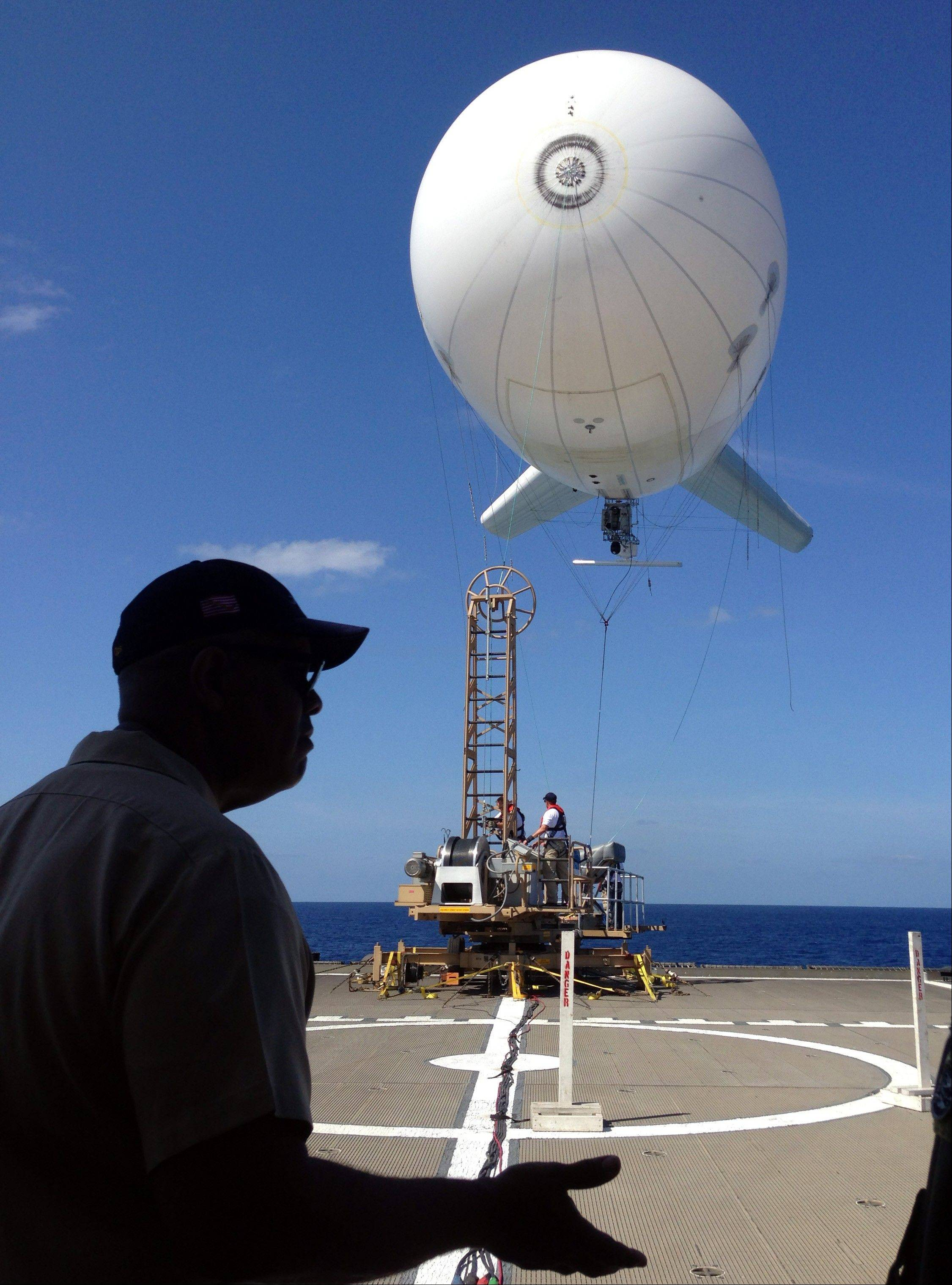 U.S. Navy Rear Admiral Sinclair Harris looks at a balloon-like craft Friday known as an aerostat that is attached to the back of his high speed vessel Swift docked in Key West, Florida.
