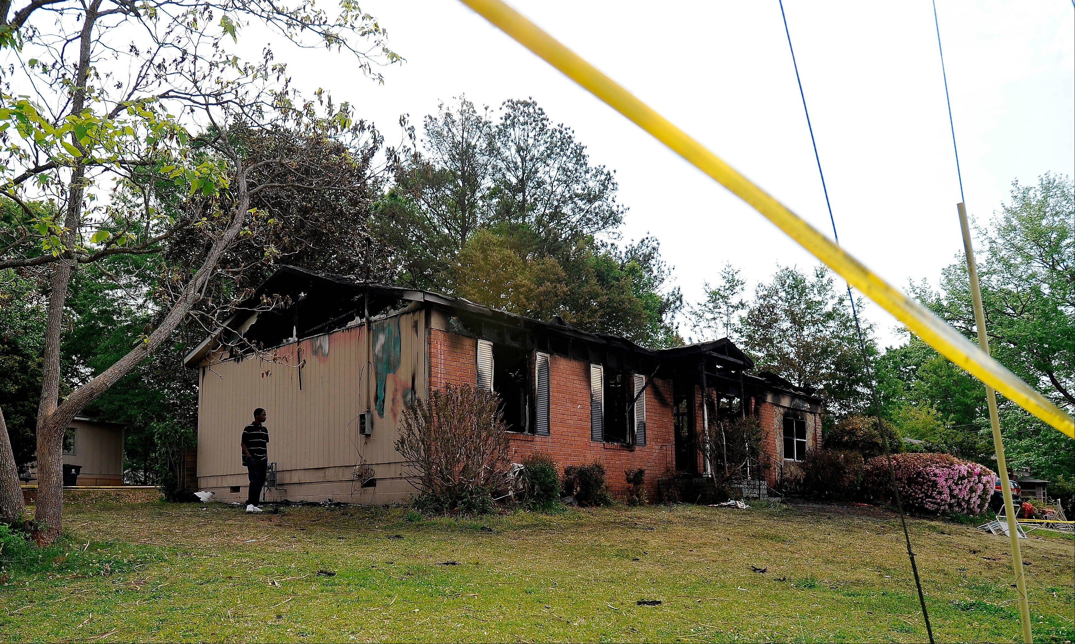 A neighbor walks past the side of a charred single-story house Saturday after a fatal fire killed five, including four children, in Newnan, Ga.