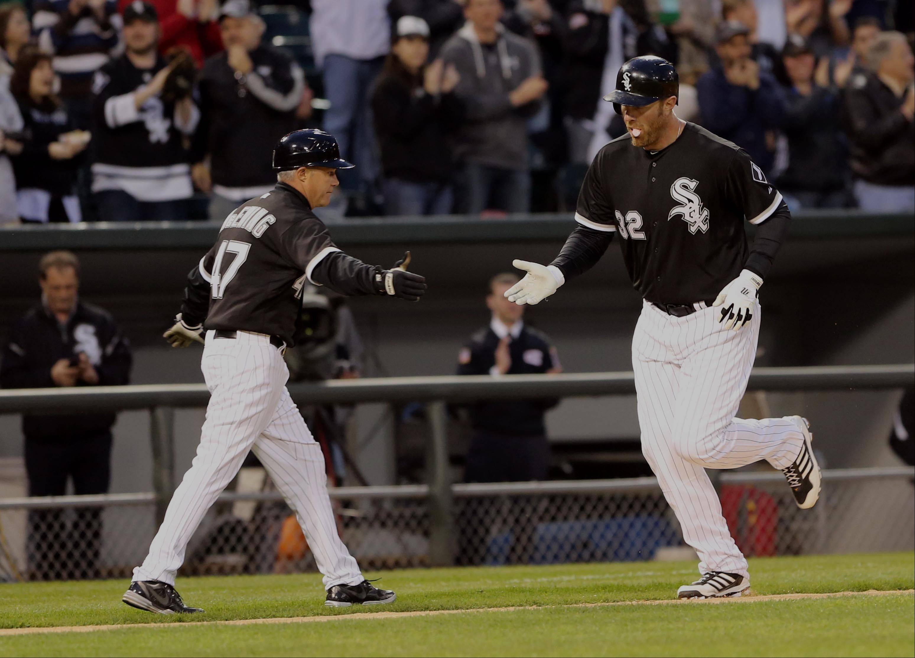 Adam Dunn shakes hands with third base coach Joe McEwing after hitting a solo home run in the fourth inning Saturday at U.S. Cellular Field.