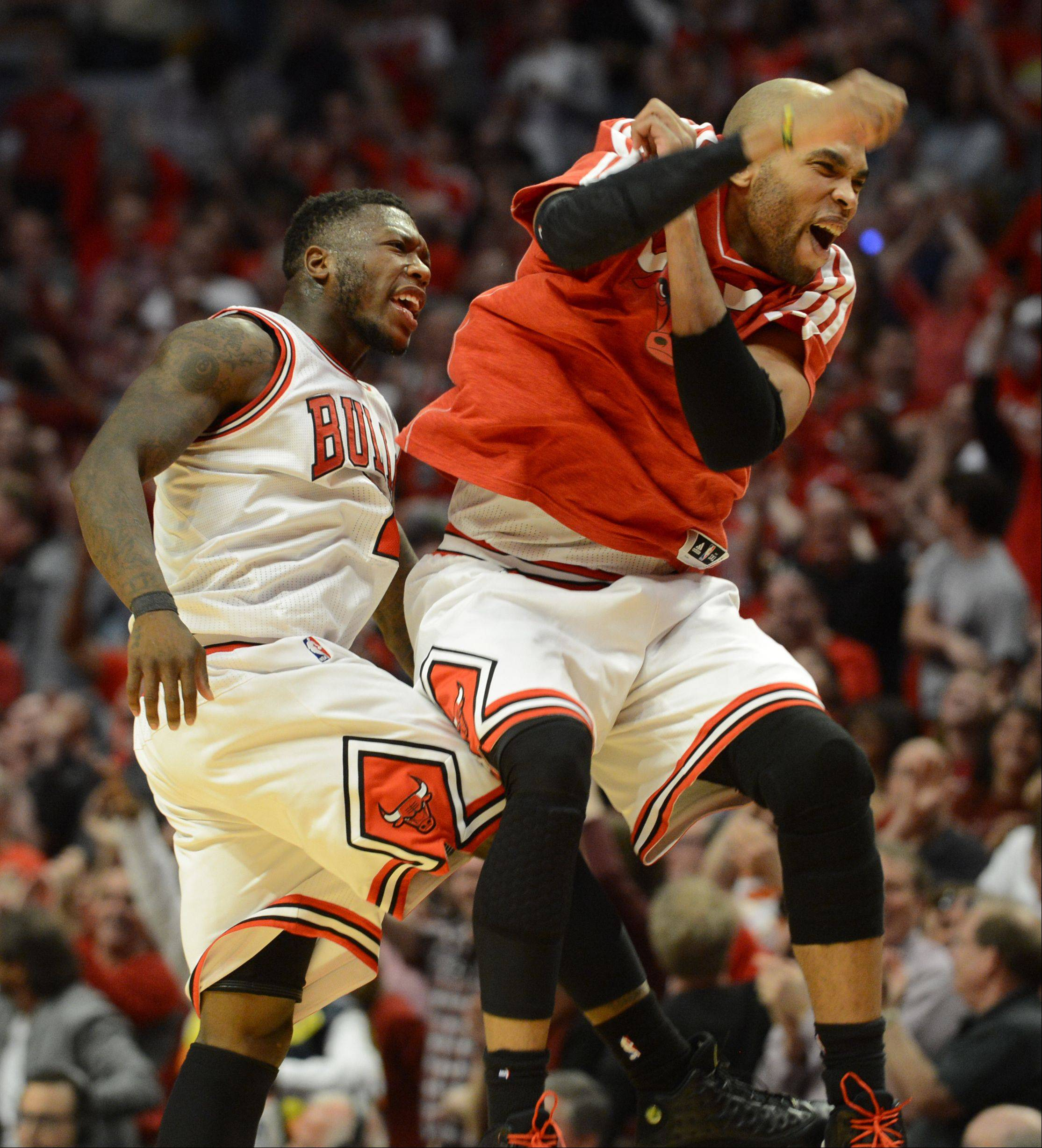 The Bulls Nate Robinson, left, and Taj Gibson celebrate Robinson's basket in the first overtime Saturday during game 4 of the first round playoff game against the Brooklyn Nets at the United Center. The Bulls won in triple overtime 142-134