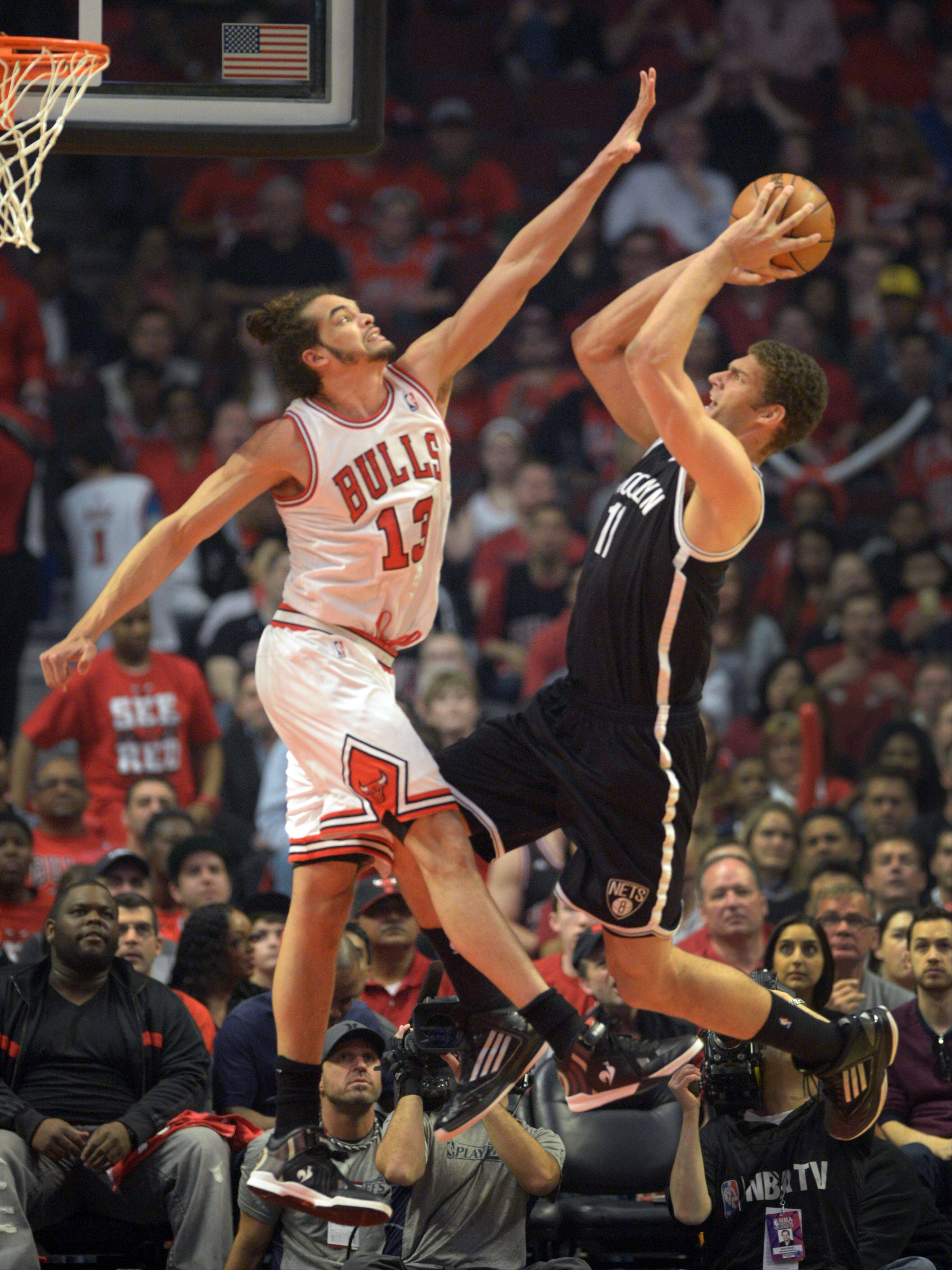 Joakim Noah, left, puts pressure on Brooklyn's Brook Lopez in first quarter action Saturday during game 4 of the first round playoff game against the Brooklyn Nets at the United Center. The Bulls won in triple overtime 142-134