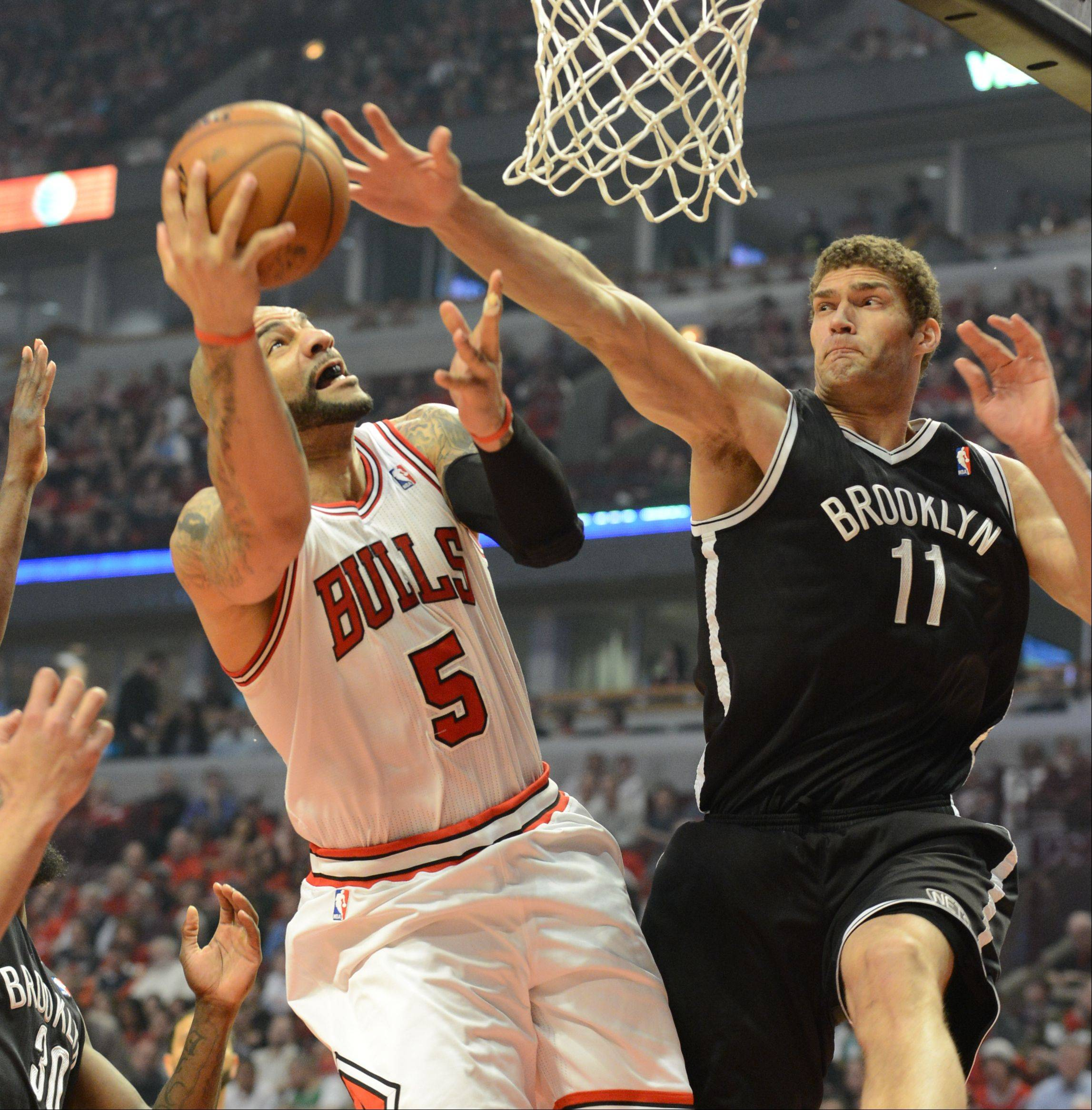 Carlos Boozer drives to the basket pressured by Brooklyn's Brook Lopez in the first half Saturday during game 4 of the first round playoff game against the Brooklyn Nets at the United Center. The Bulls won in triple overtime 142 - 134.