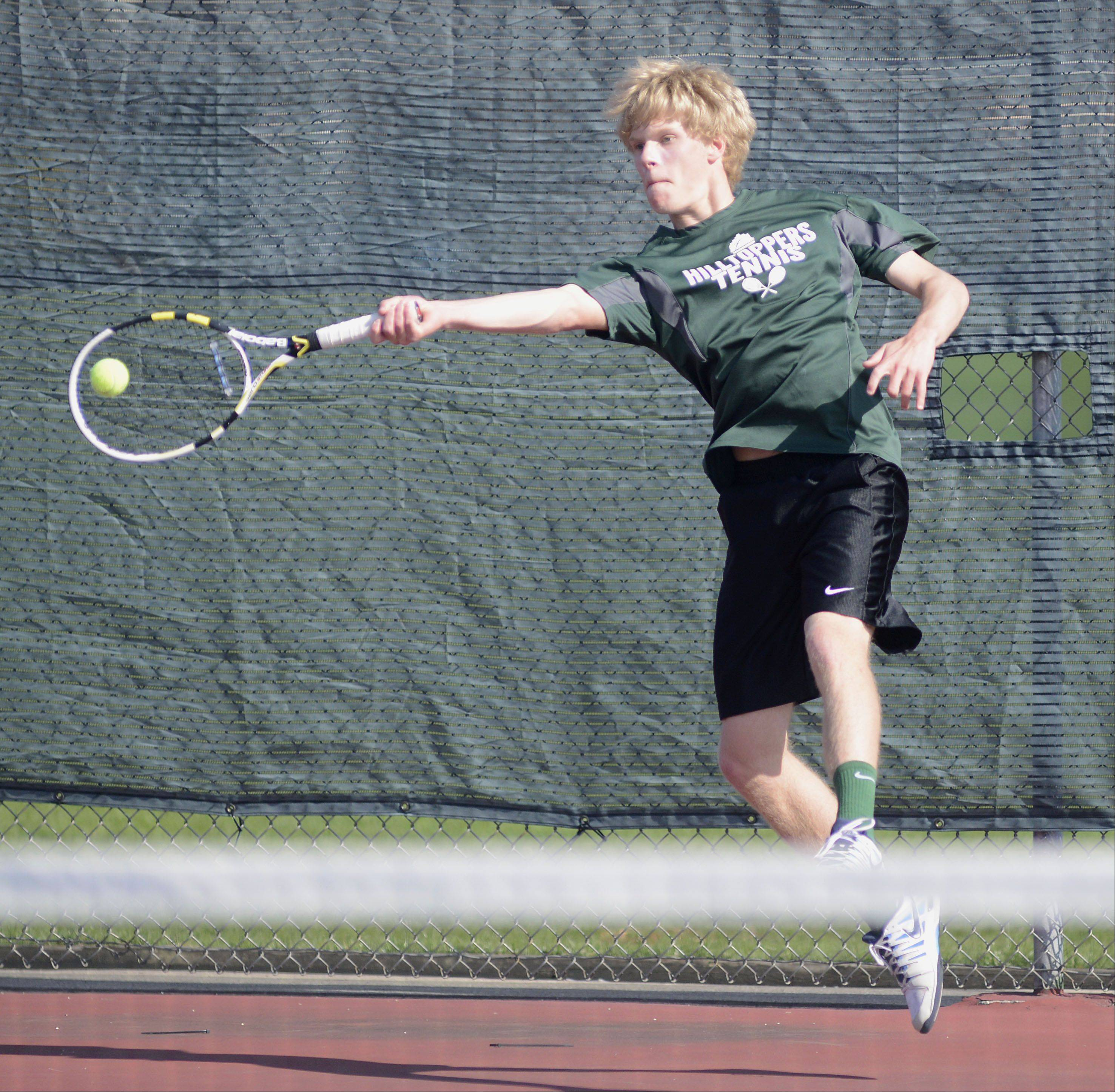 Glenbard West's Kenny Reick leaps to return a hit to St. Charles East in the first doubles match at West Aurora High School on Saturday, April 27.