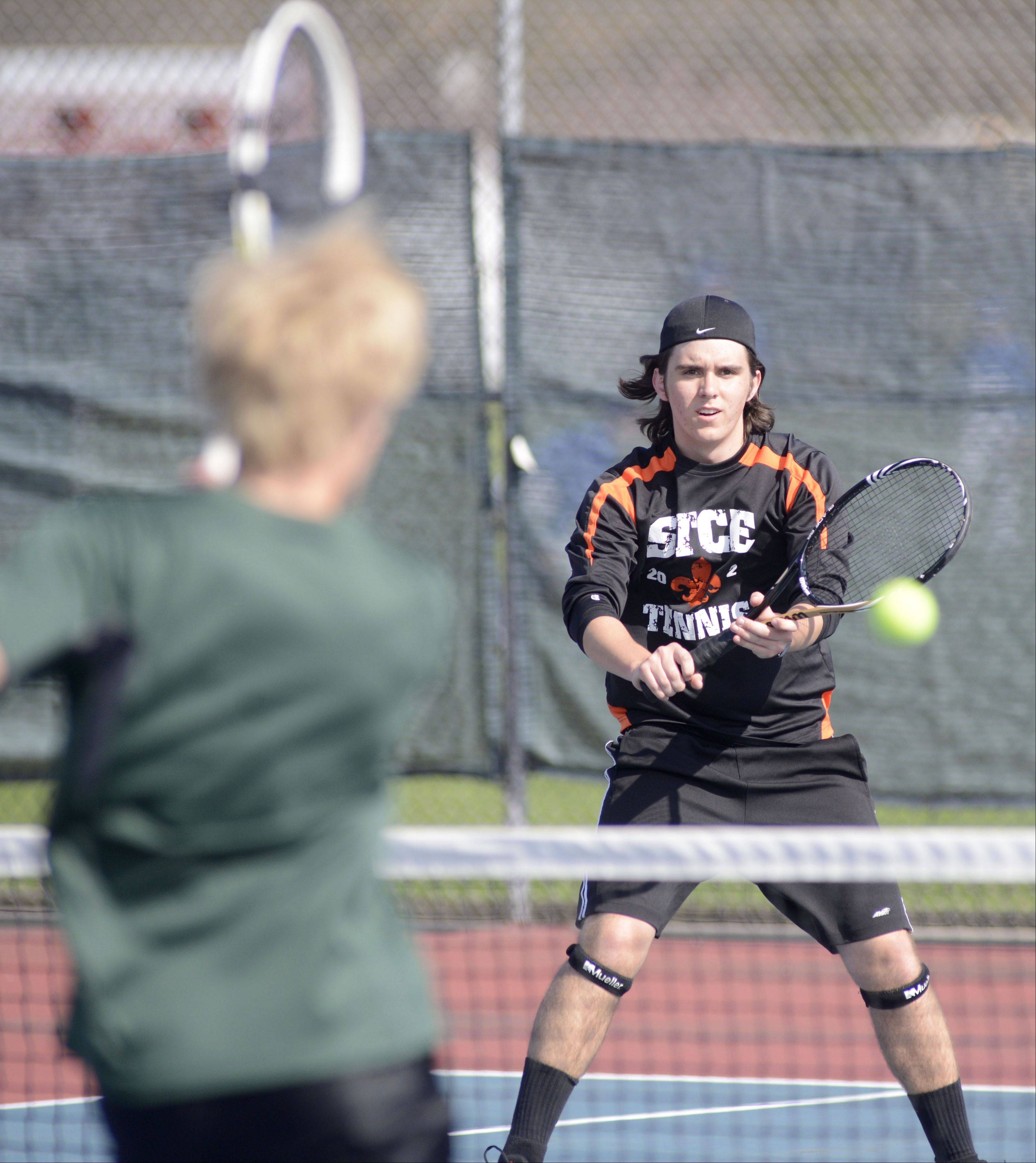 St. Charles East's George Spoerl times his return of the ball from Glenbard West's Kenny Reick in the first doubles match at West Aurora High School on Saturday, April 27.