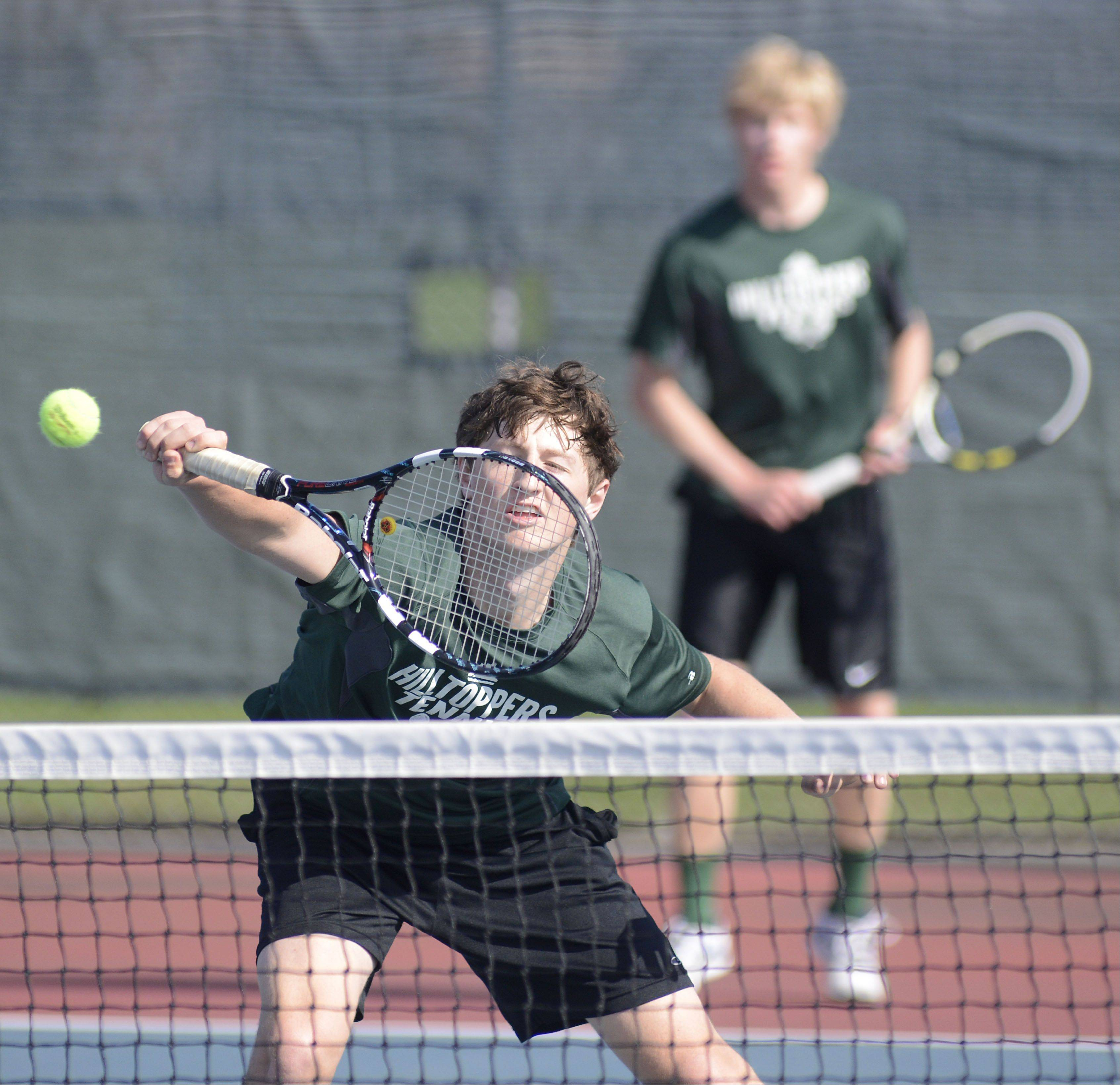 Glenbard West's Jack Kellenberger is quick to return a hit to St. Charles East in the first doubles match with teammate Kenny Reick at West Aurora High School on Saturday, April 27.