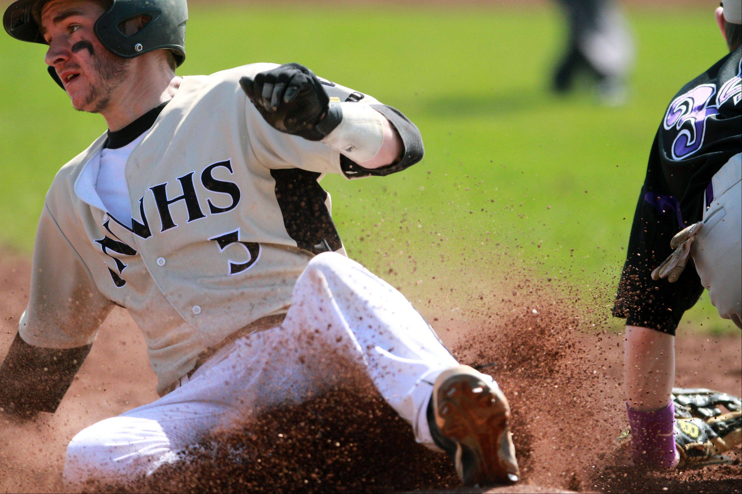 Grayslake North shortstop Carl Russell is safe at third base as Hampshire third baseman RJ Consigny waits for the throw at Grayslake North on Saturday. Russell ended up scoring on a hit.