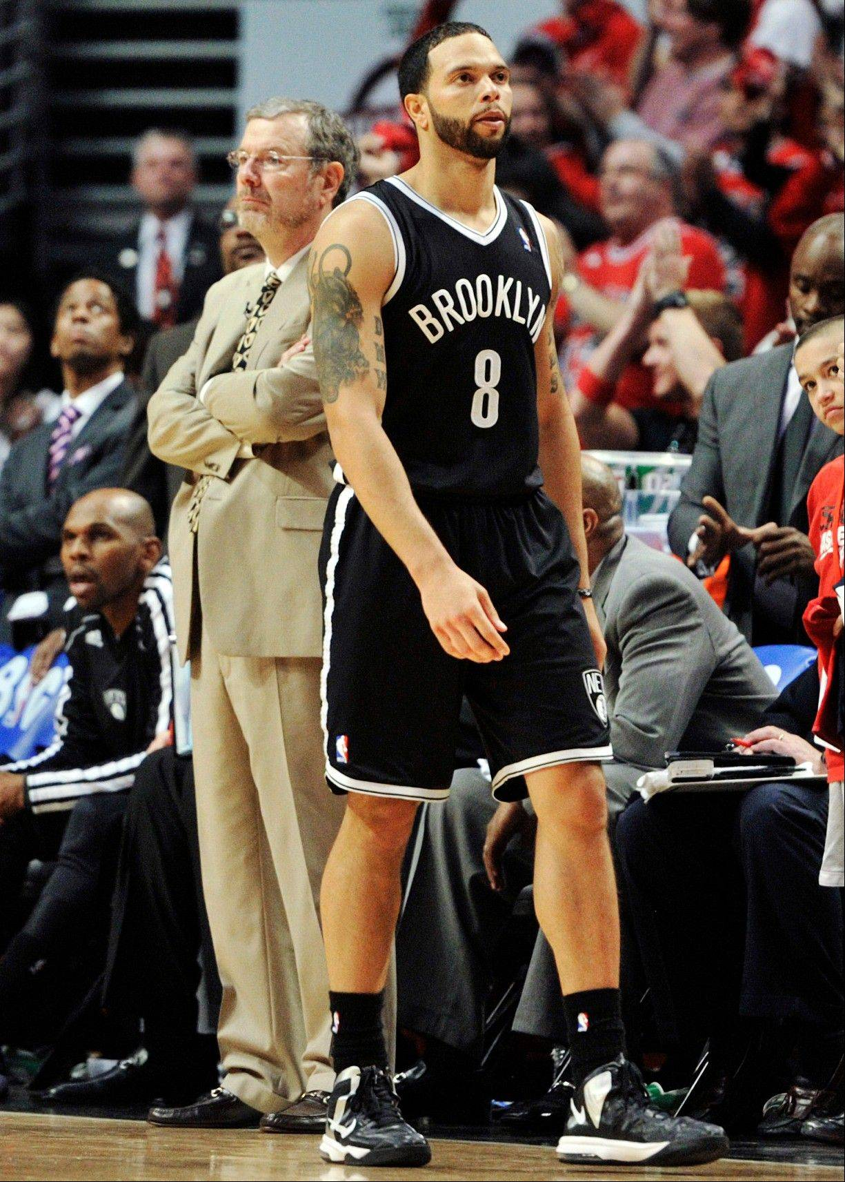 Brooklyn Nets head coach P.J. Carlesimo, rear left, stands on the court as Nets' Deron Williams (8) walks past the bench in the closing seconds during the third overtime in Game 4 of their first-round NBA basketball playoff series against the Chicago Bulls on Saturday, April 27, 2013, in Chicago. The Bulls won 142-134 in three overtimes.