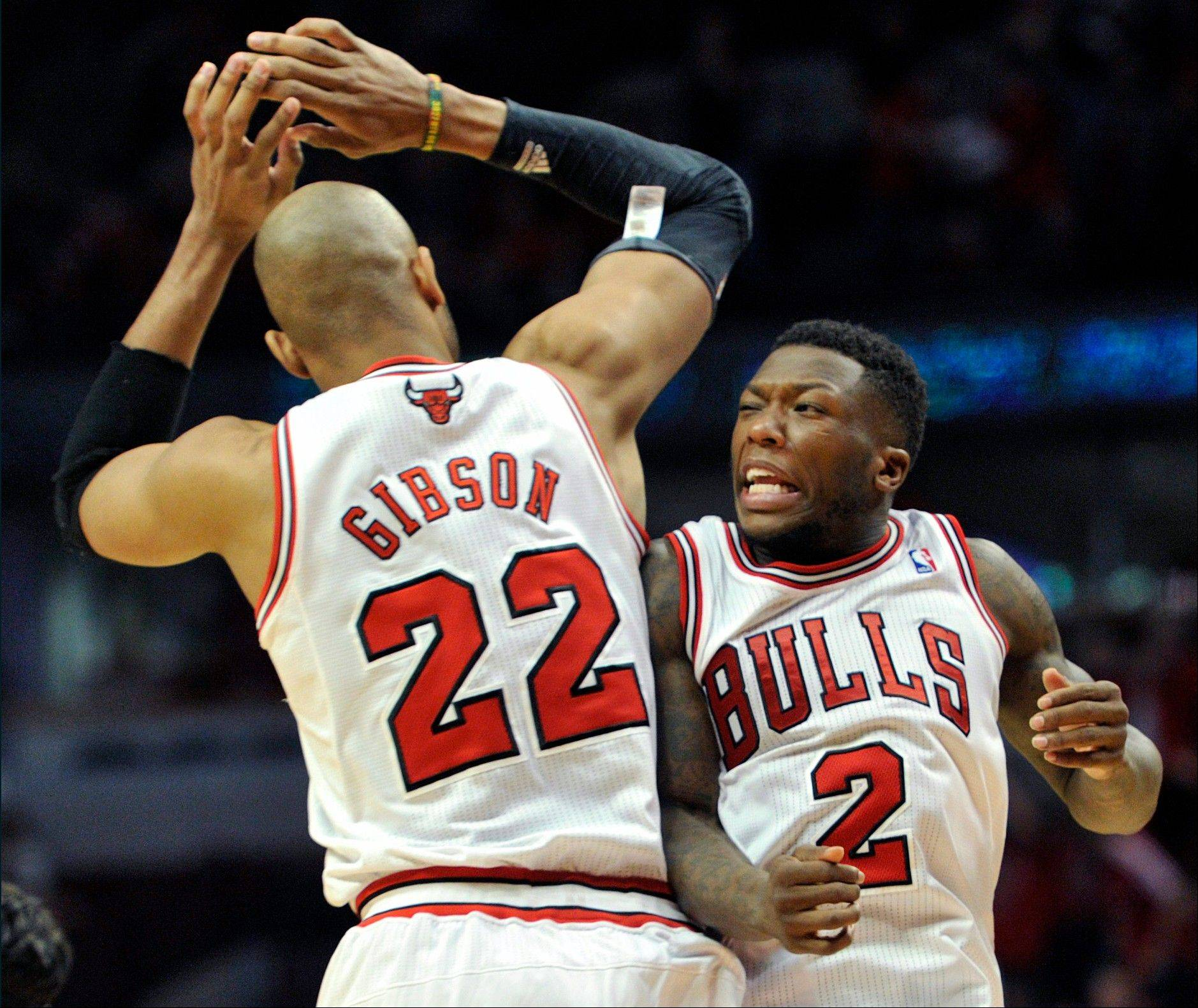 Chicago Bulls' Taj Gibson (22) and Nate Robinson (2) celebrate a basket against the Brooklyn Nets during the second overtime in Game 4 of their first-round NBA basketball playoff series Saturday, April 27, 2013, in Chicago. The Bulls won 142-134 in three overtimes.