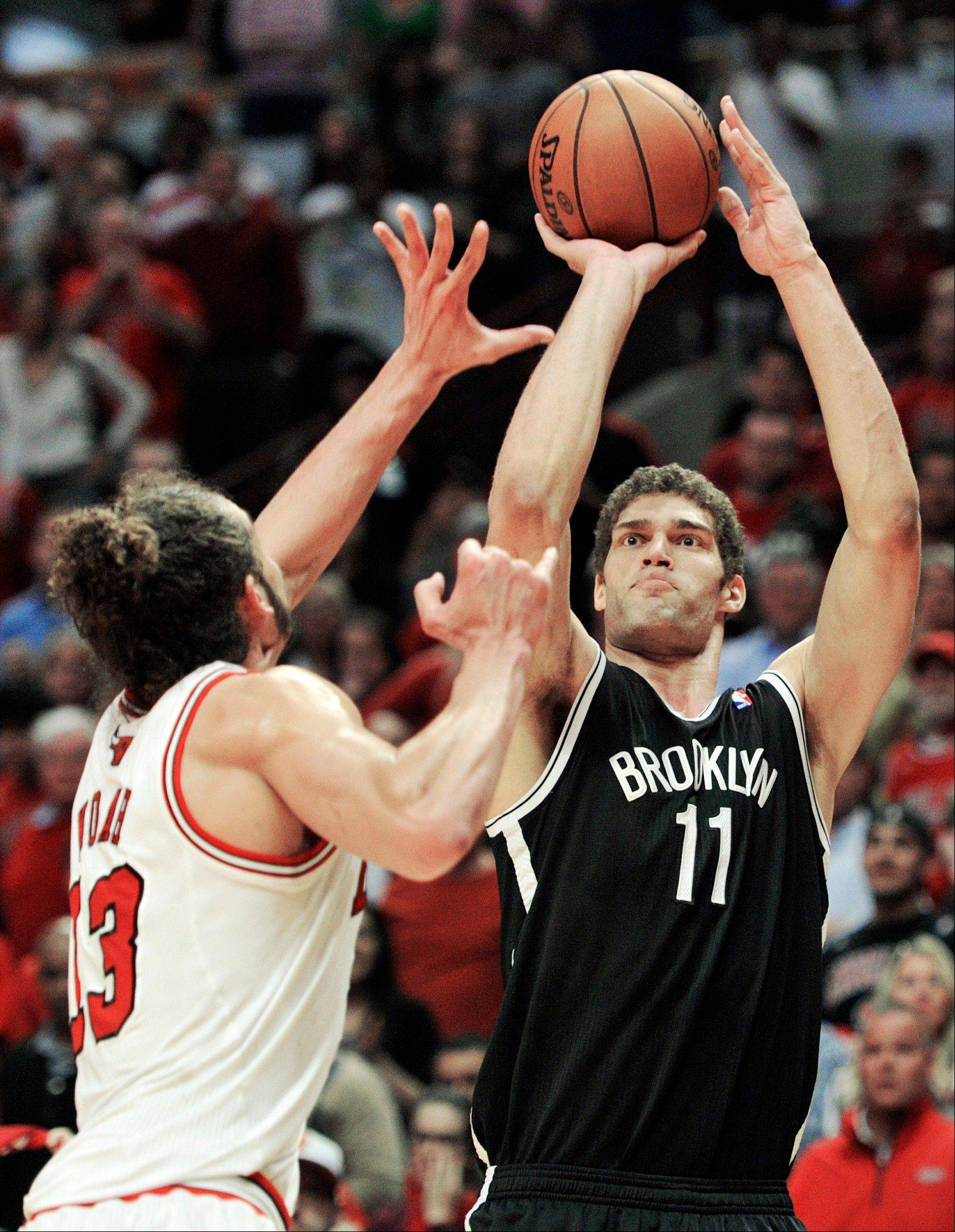 Chicago Bulls' Joakim Noah, left, tries to block the shot of Brooklyn Nets' Brook Lopez (11) during the second overtime in Game 4 of their first-round NBA basketball playoff series Saturday, April 27, 2013, in Chicago. The Bulls won 142-134 in three overtimes.