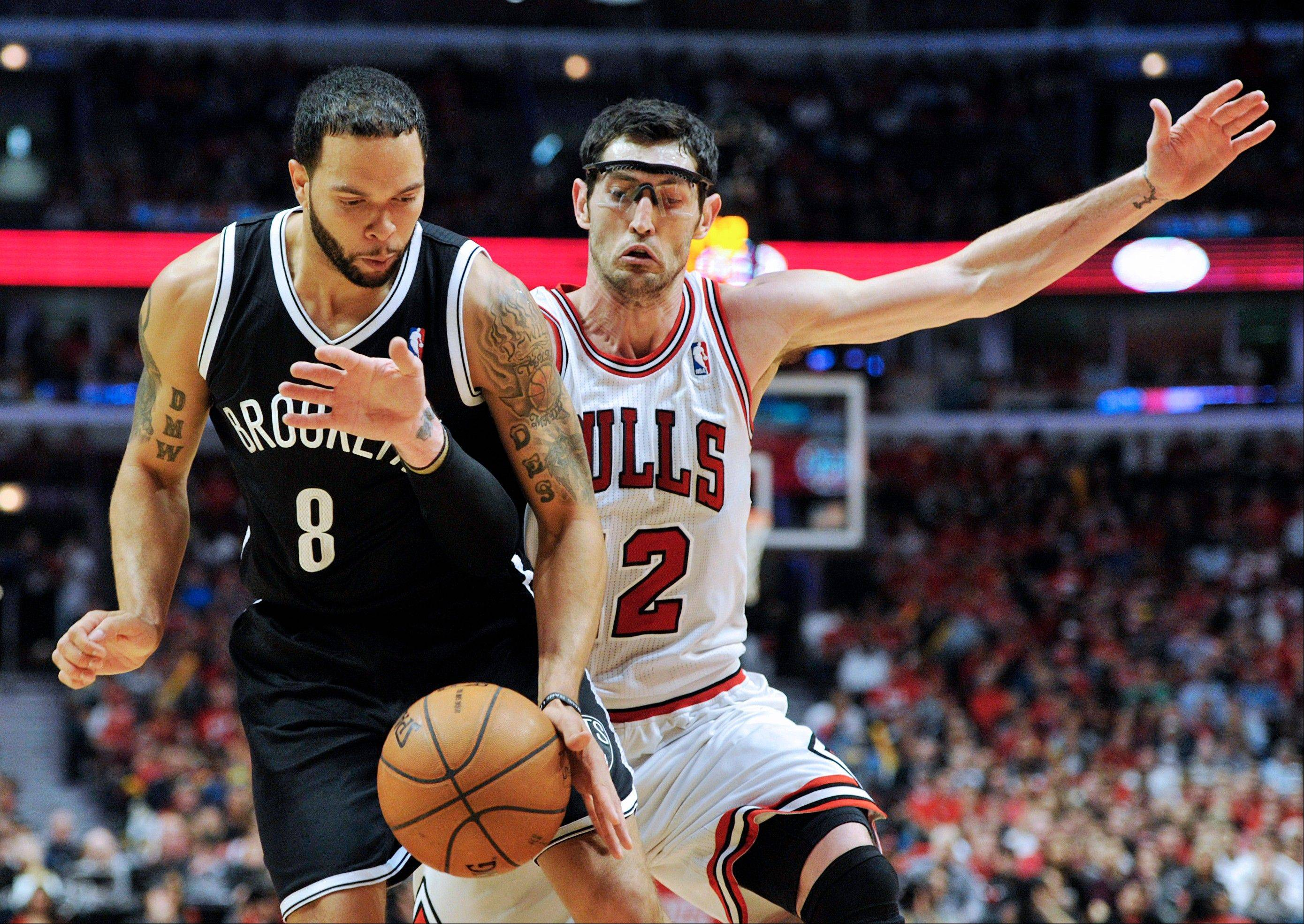 Brooklyn Nets' Deron Williams (8) and Chicago Bulls' Kirk Hinrich (12) scramble for the ball during the second half in Game 4 of their first-round NBA basketball playoff series Saturday, April 27, 2013, in Chicago. The Bulls won 142-134 in three overtimes.