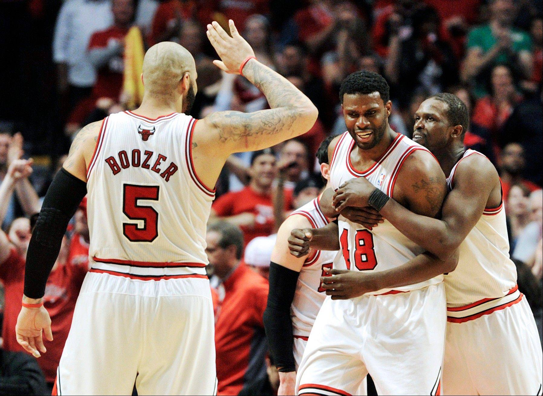 Chicago Bulls' Nazr Mohammed (48) celebrates a late basket with teammates Carlos Boozer (5) and Luol Deng during the third overtime in Game 4 of their first-round NBA basketball playoff series against the Brooklyn Nets Saturday, April 27, 2013, in Chicago. The Bulls won 142-134 in three overtimes.