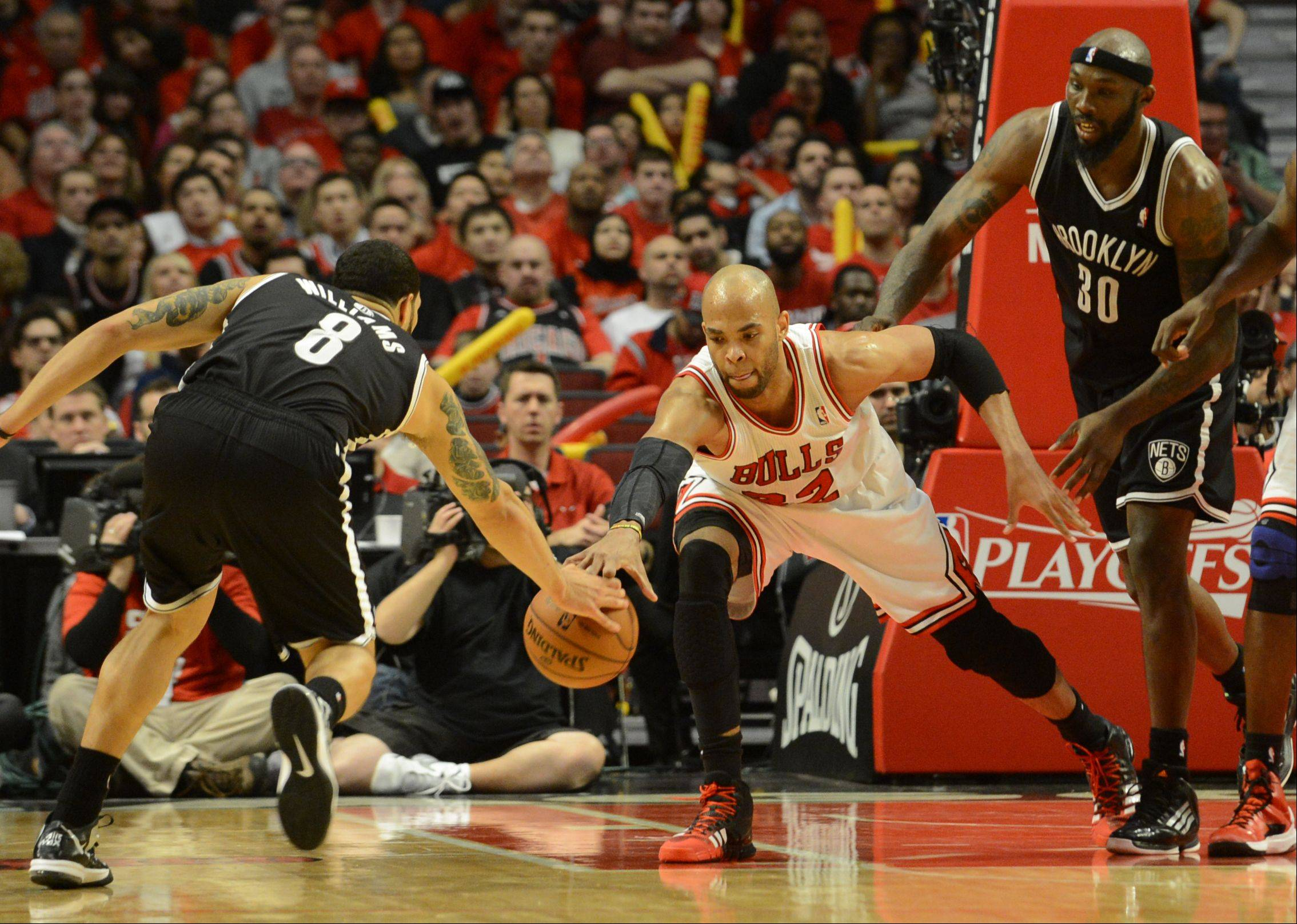 The Bulls Taj Gibson goes for the ball against Brooklyn's Deron Williams, left, Saturday during game 4 of the first round playoff game against the Brooklyn Nets at the United Center. The Bulls won in triple overtime 142-134