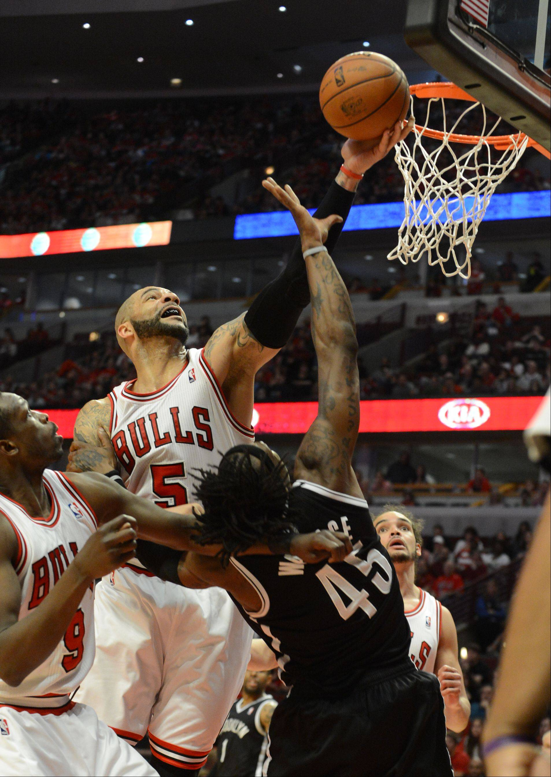 The Bulls Carlos Boozer blocks a shot by Brooklyn's Gerald Wallace in the 4th quarter Saturday during game 4 of the first round playoff game against the Brooklyn Nets at the United Center. The Bulls won in triple overtime 142-134